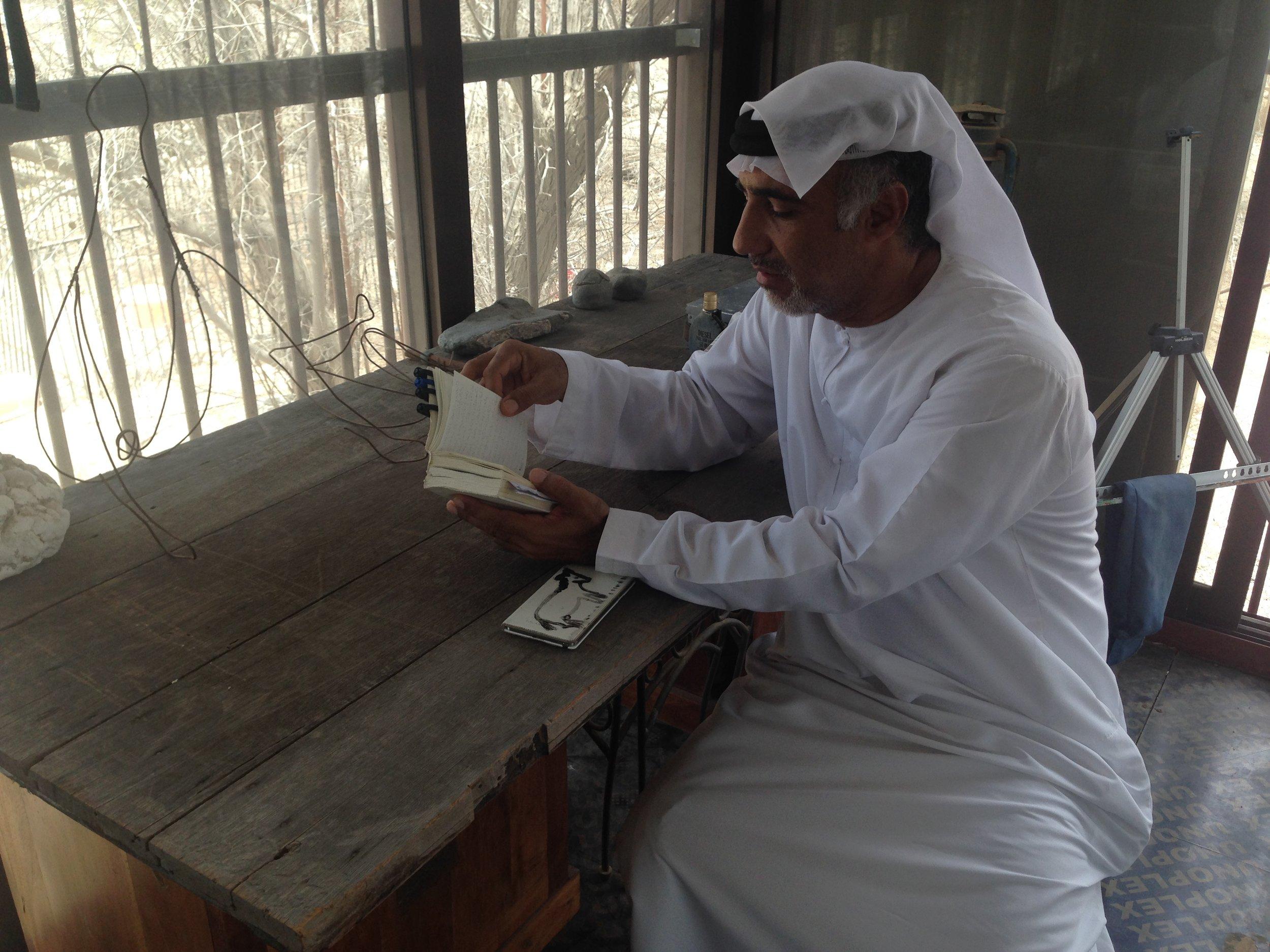 Abdullah Al Saadi sits inside his studio. Image by Anna Seaman