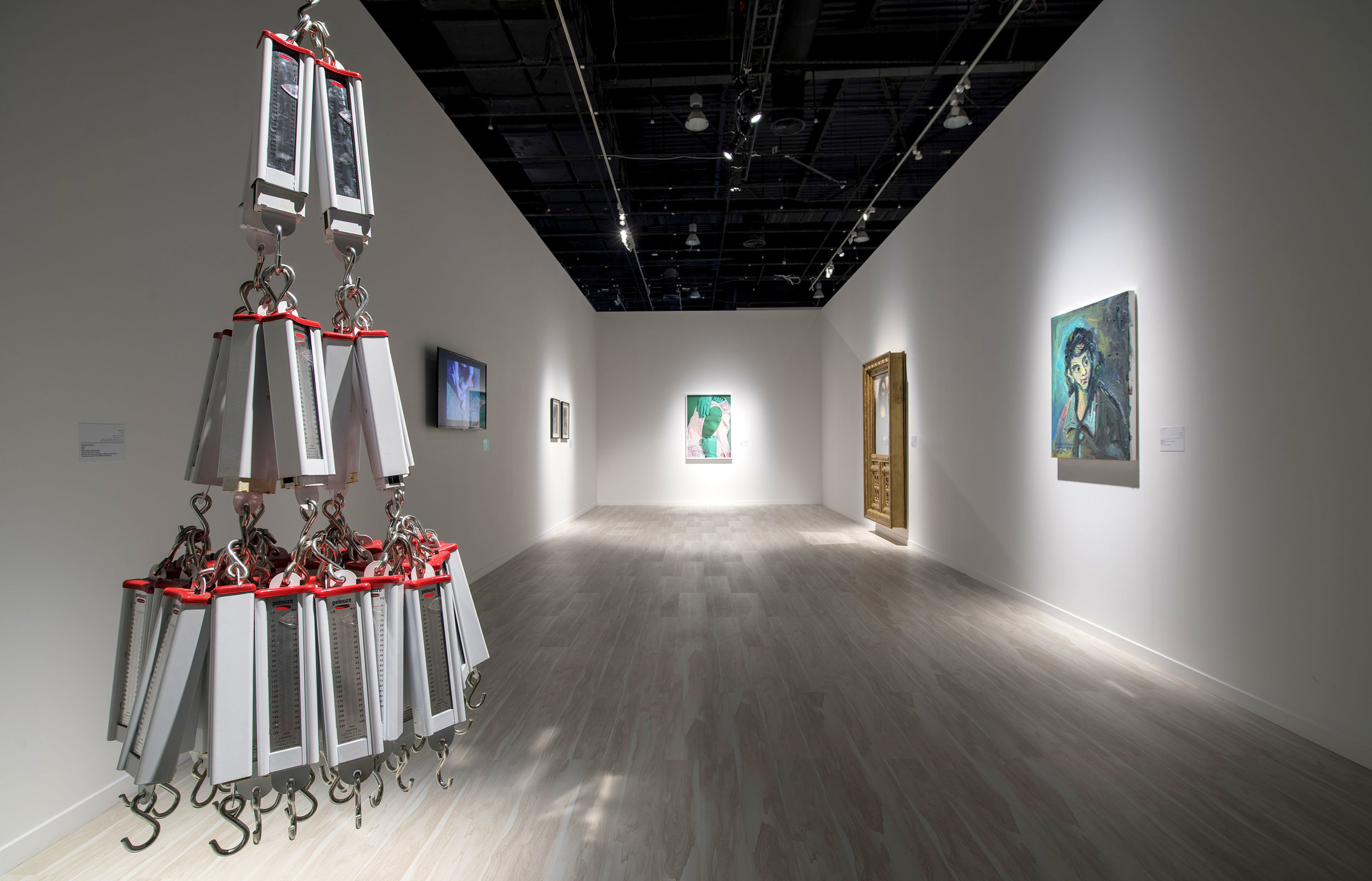 Mohammed Kazem's Scale hangs in the first section of Emirati art. On the right, Hassan Sharif's painting of El Greco is visible.  © Courtesy of Abu Dhabi Festival