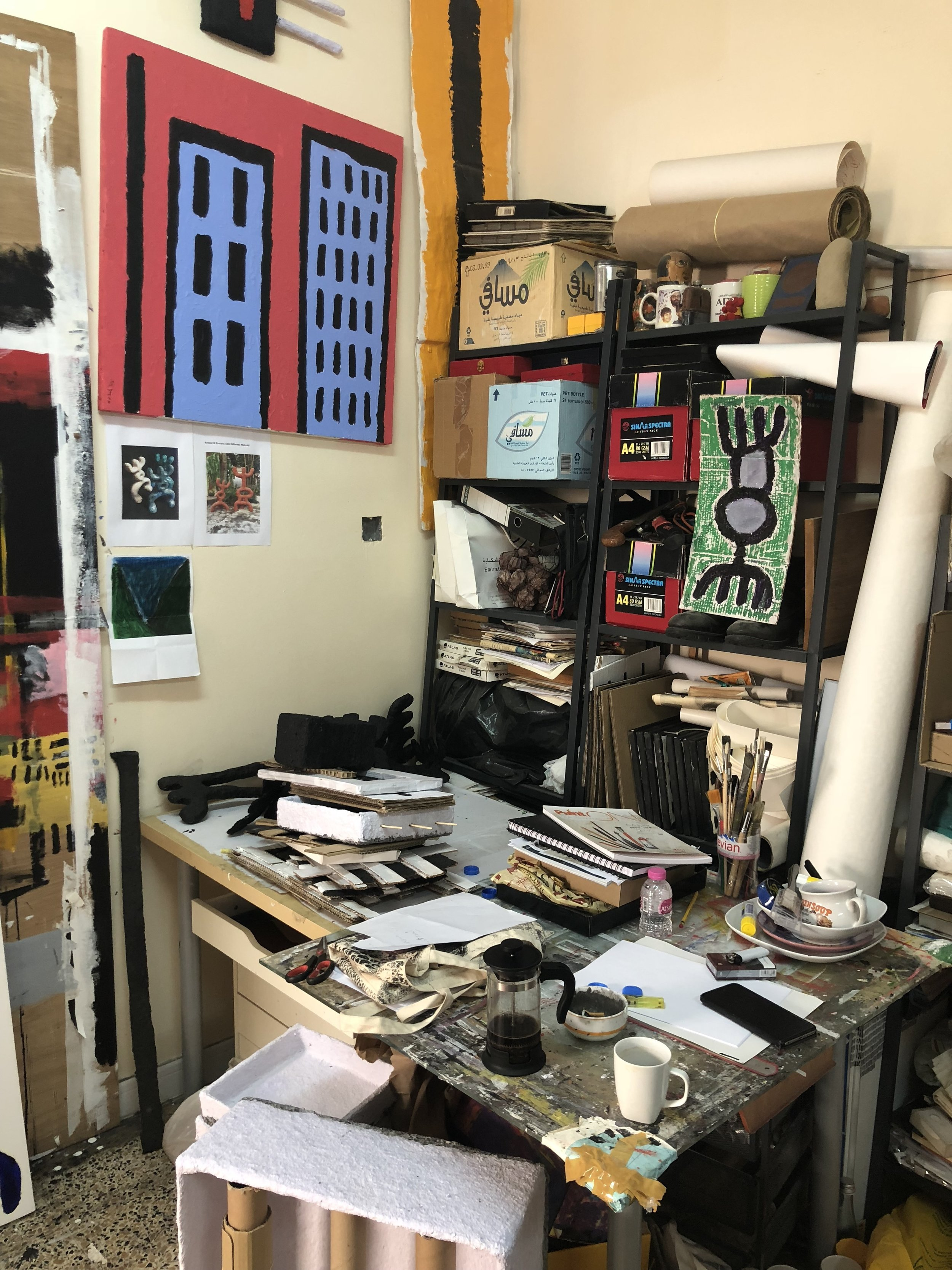 Inside Mohammed Ahmed Ibrahim's studio, his desk is filled with evidence of his daily practice and the walls are hung from ceiling to floor with sketches and canvases. Image taken by Anna Seaman.