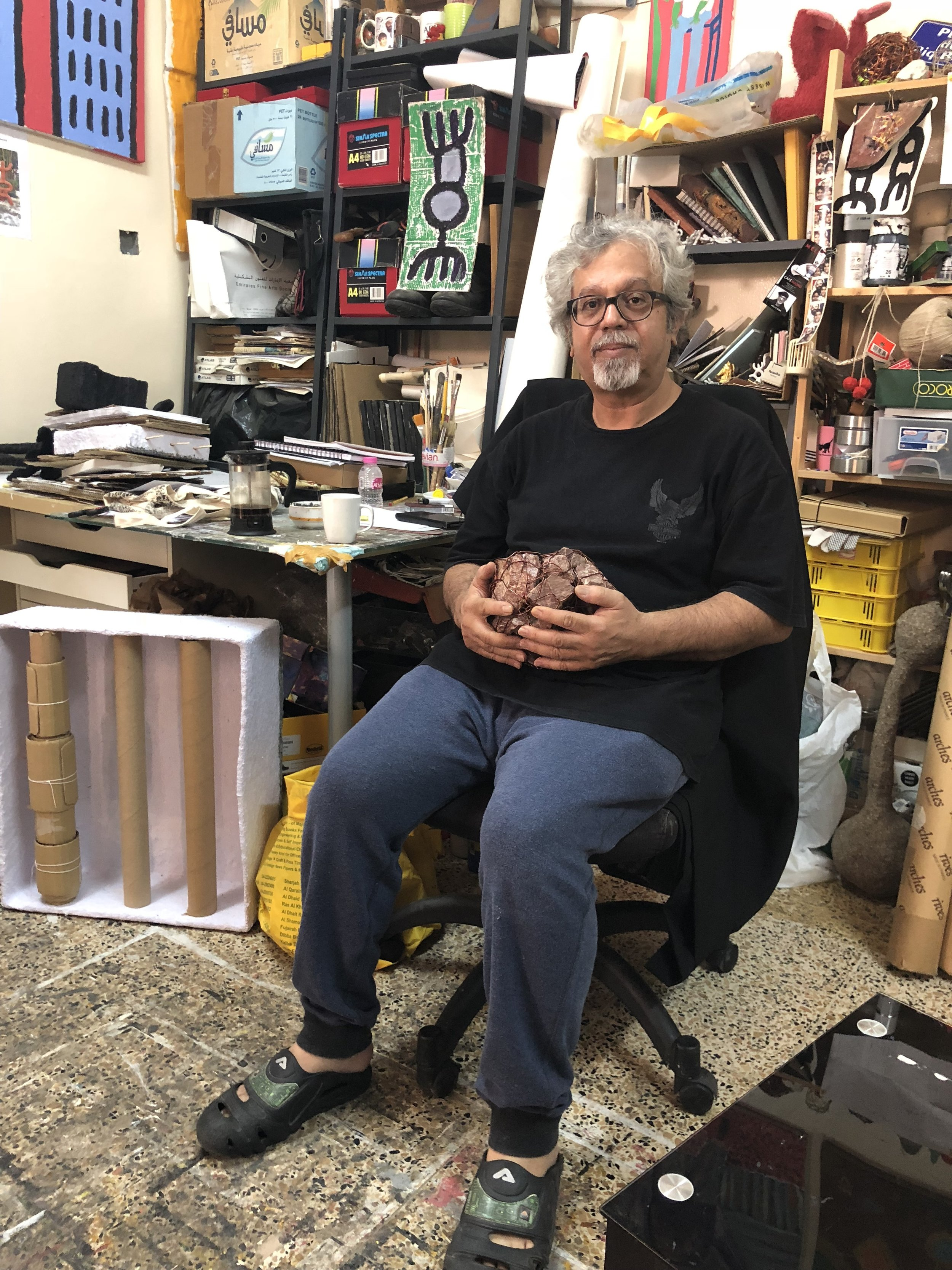 Mohammed Ahmed Ibrahim in his home studio, holding one of his collections of rocks. Image taken by Anna Seaman.