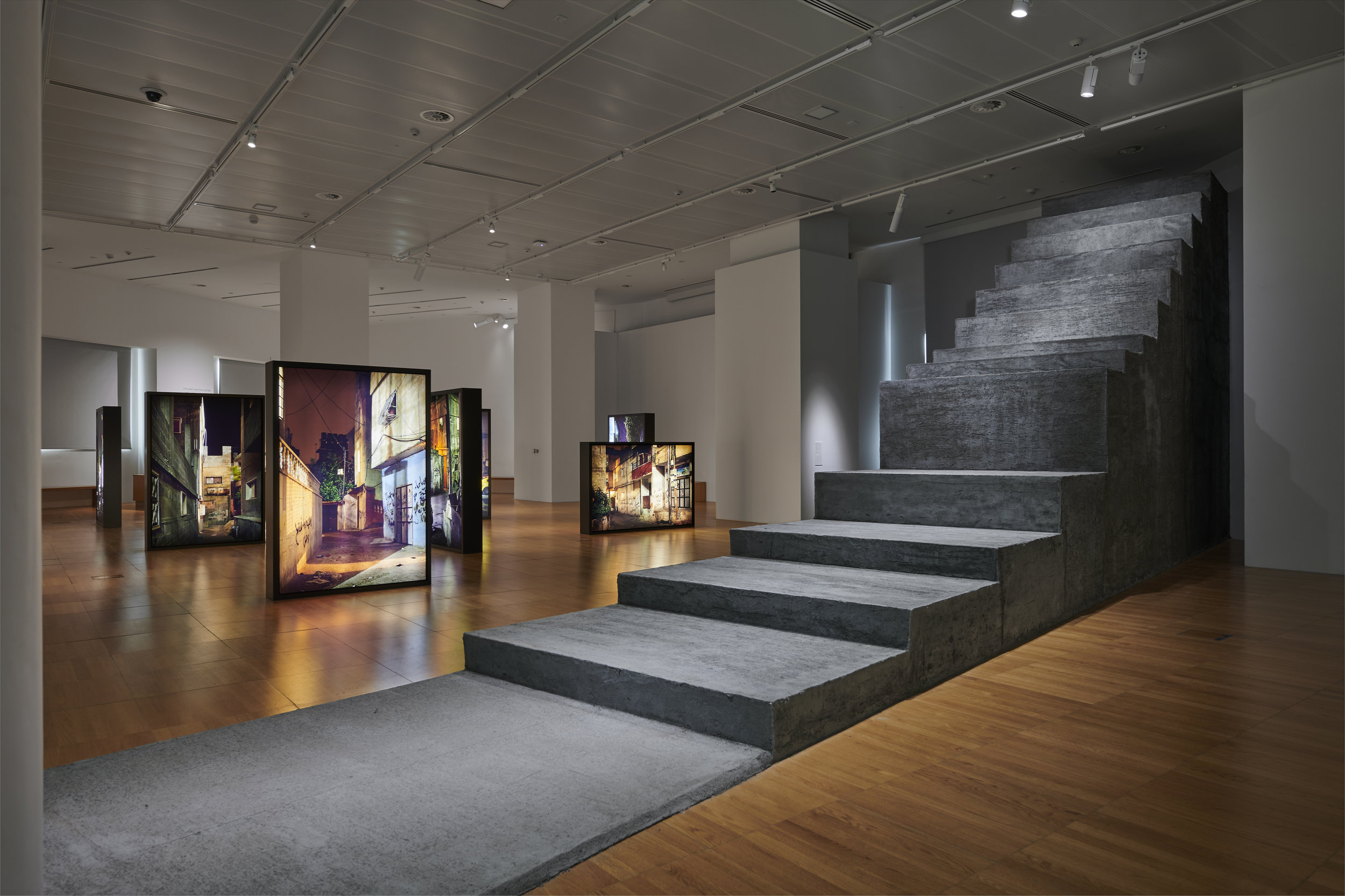 Sandi Hilal and Alessandro Petti. Common Assembly (front) and  Refugee Heritage (back),2018. Concrete structure, photos and light boxes, variable dimensions. Courtesy of the Artists and NYU Abu Dhabi Art Gallery. Image by John Varghese