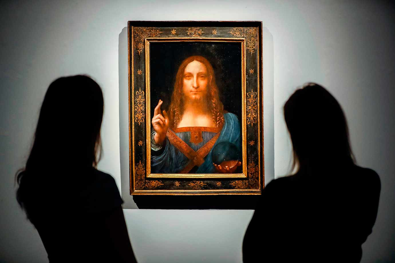 Christie's employees pose in front of Salvator Mundi by Leonardo da Vinci. Image Credit:AFP