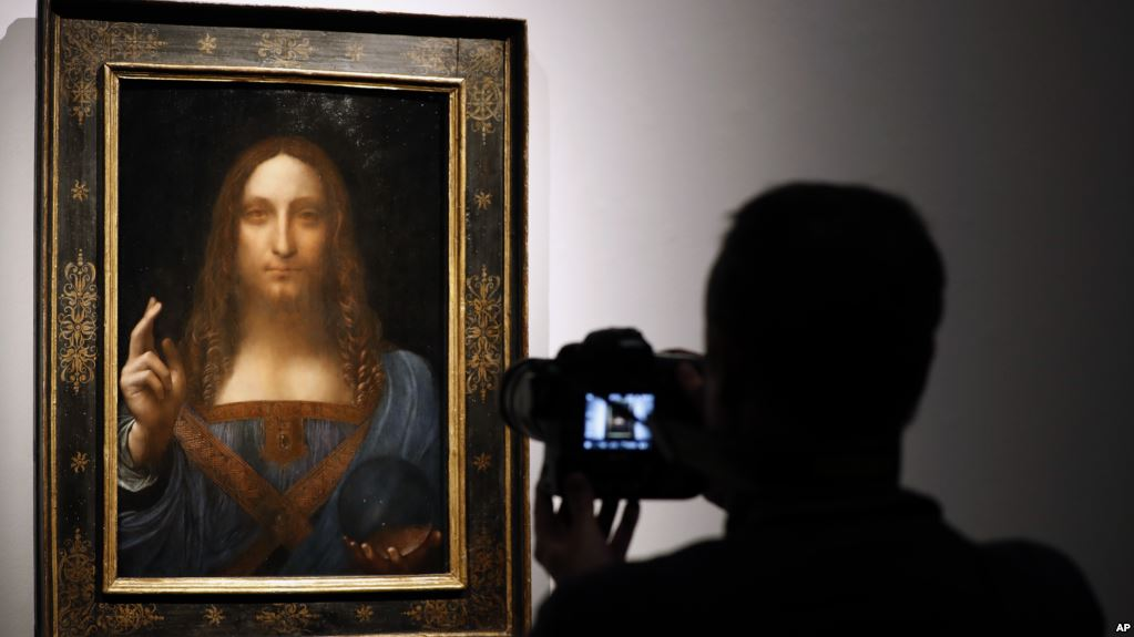 "A visitor films Leonardo da Vinci's ""Salvator Mundi"" on display at Christie's auction rooms, in London, Oct. 24, 2017. Image Credit: AP"