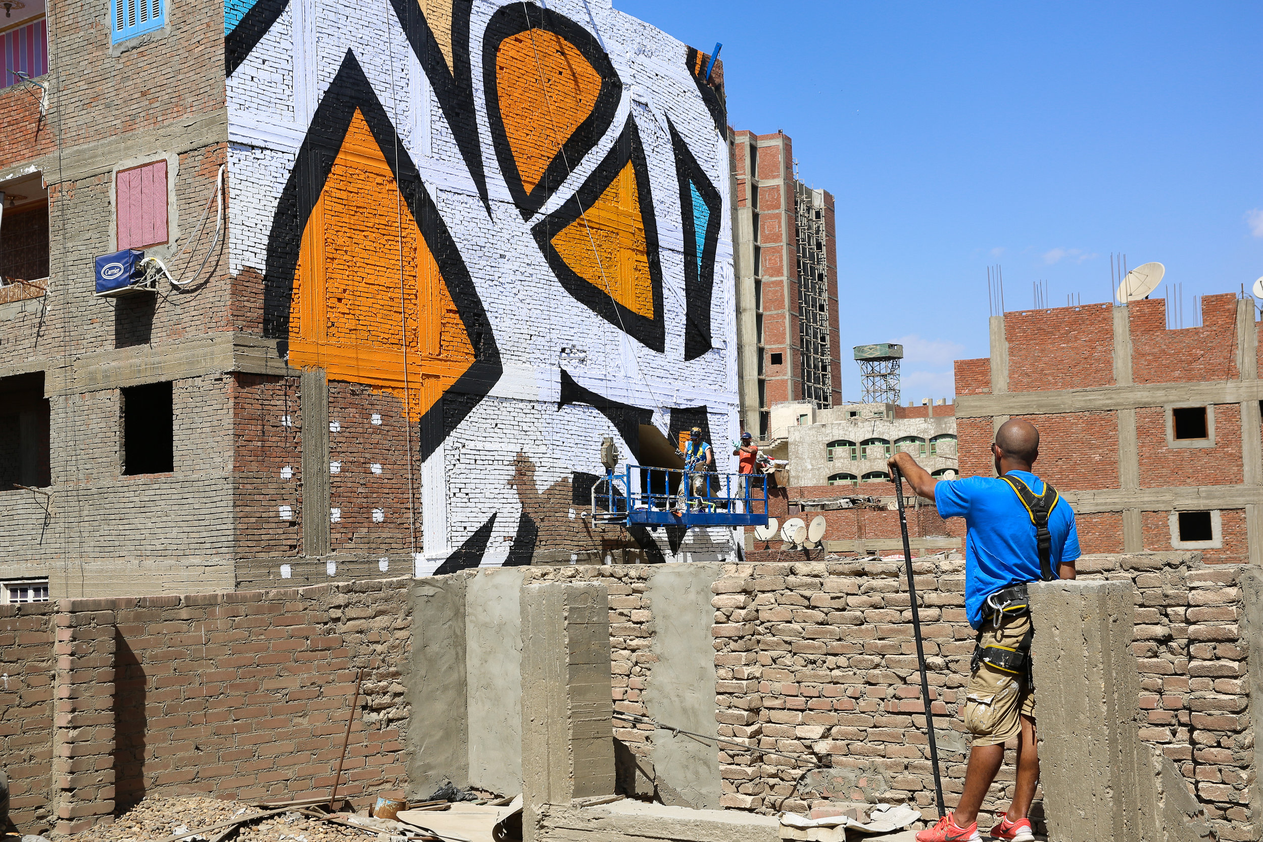 eL Seed, seen here in the foreground working on his most ambitious project to date, the mural in Cairo. Courtesy of eL Seed Studio.