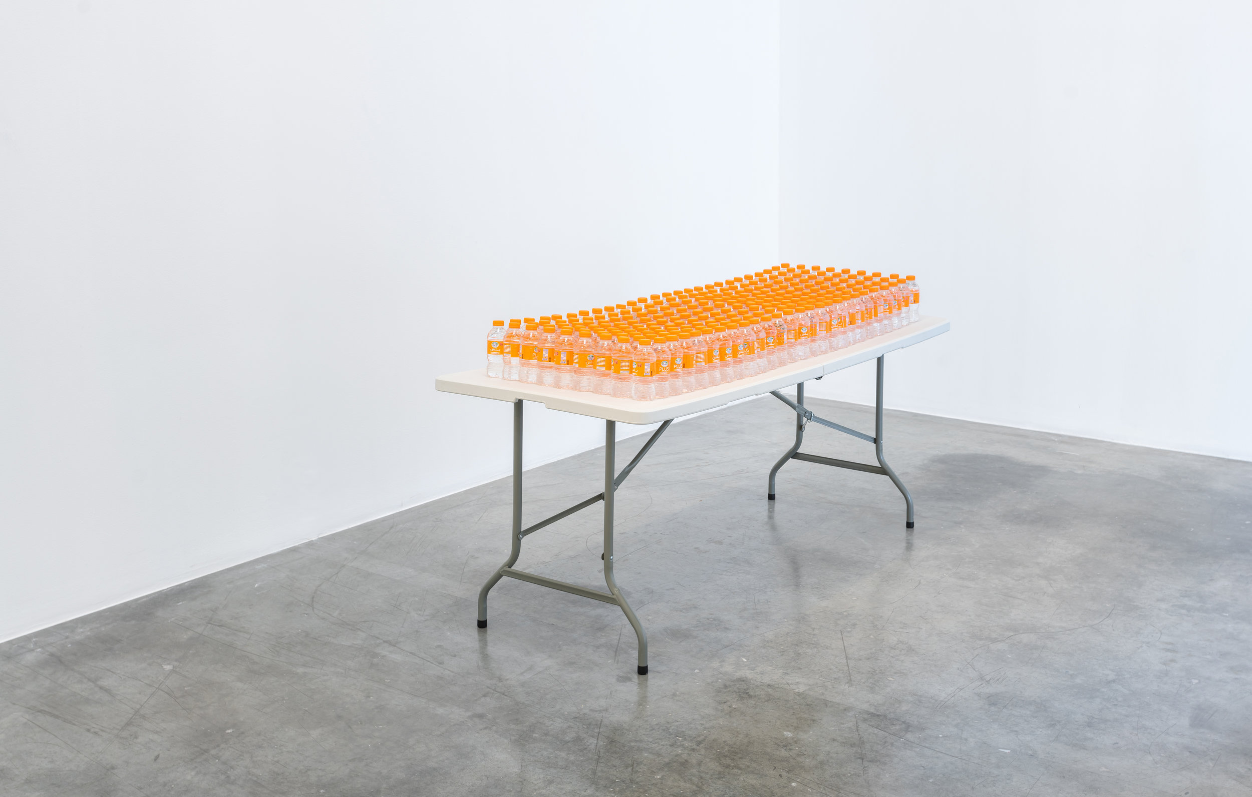 SUNSHINE, 2018, water bottles, table, Al Ain Vitamin D water bottles on a plastic folding table, dimensions variable. Image courtesy of the artist and Grey Noise.