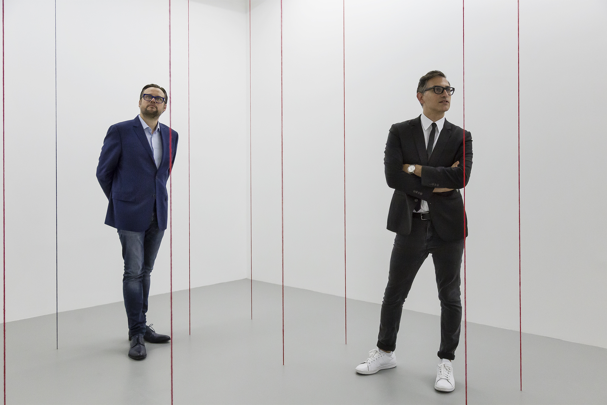 Sam Bardaouil & Till Fellrath stand inside Fred Sandback's work inside their Ways of Seeing exhibition.