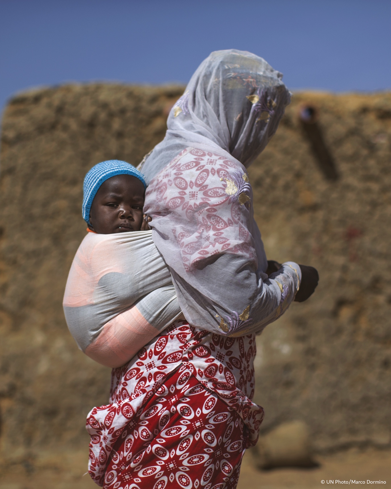 In Mali, a woman and her child displaced by violence in Timbuktu in 2015 walk through a village for internally displaced people in Mopti. Courtesy UN Photo/Marco Dormino.