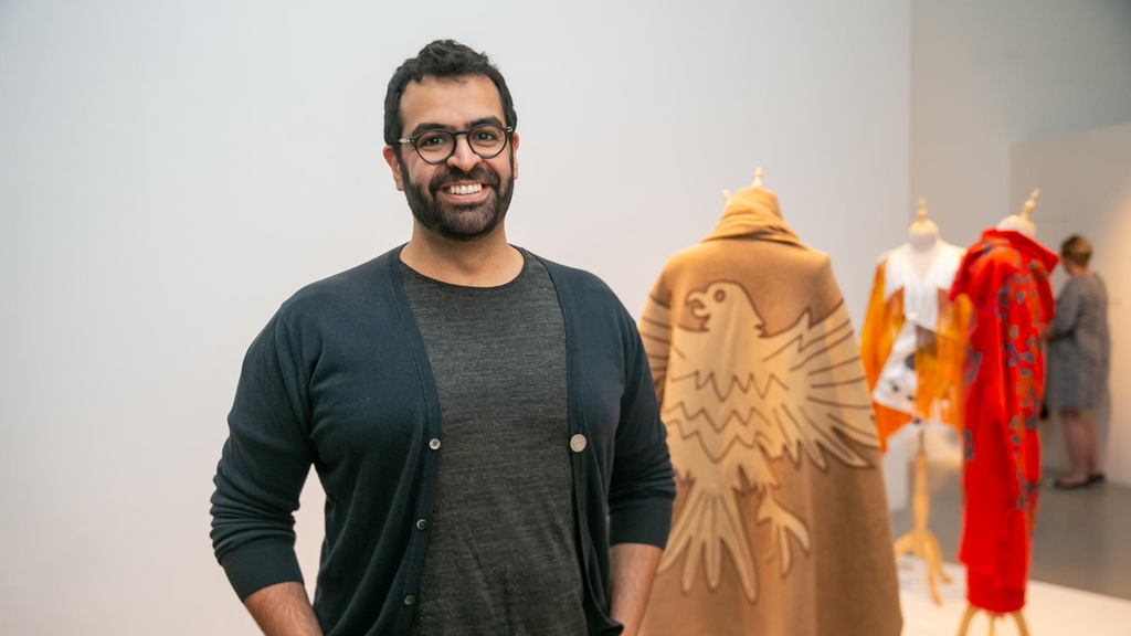 Khalid Mezaina stands infront of his work at Tashkeel's The Alumni Return. He has graduated with a master's degree in textile design from Rhode Island School of Design. Image courtesy of Tashkeel.