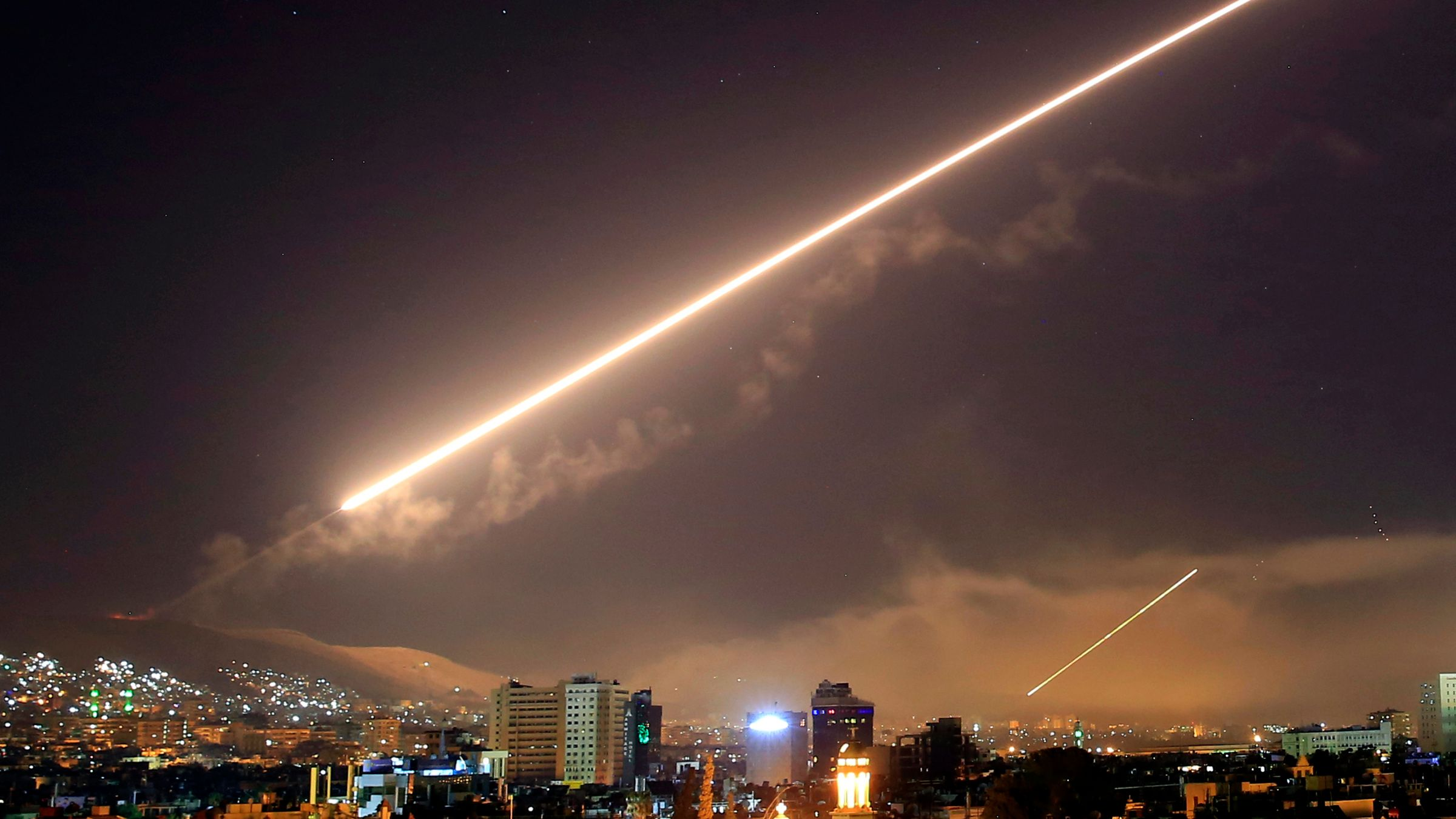 Amber chrome reminiscent of the 'Shock and Awe' bombing of Baghdad in 2003, surface-to-air missiles illuminate the night sky of Damascus.    AP Photo/Hassan Ammar