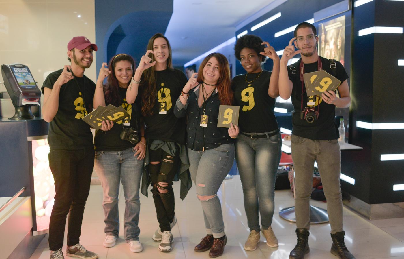 Equipo de voluntarios del festival haciendo el símbolo de la Garra de oro y luciendo algunas de las aplicaciones.