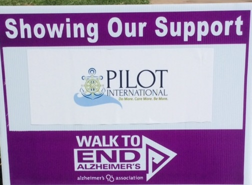 Pilot International logo on a Walk to End Alzheimer's sign.