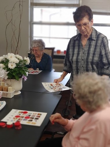 Pilot member Donna Kimber assists residents at Mediclodge. play Brain O Bingo.