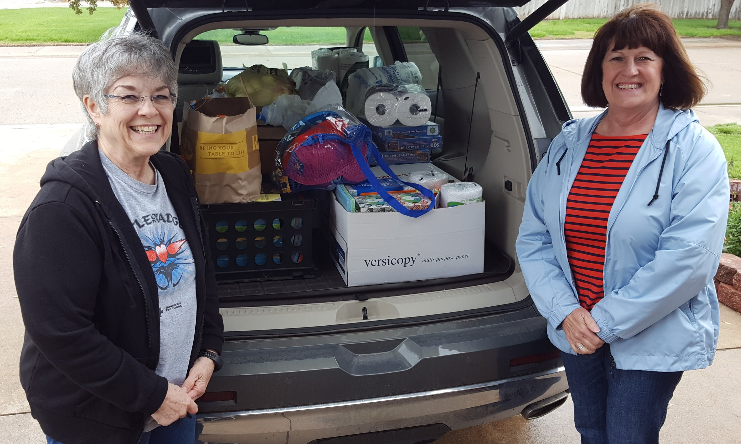 Betty Schneider (projects chair) presents a van load of items collected at Pilot Club Spring Convention plus 9 digital cameras and $1150.00 in checks & gift cards to Gail Moeder from Camp Hope