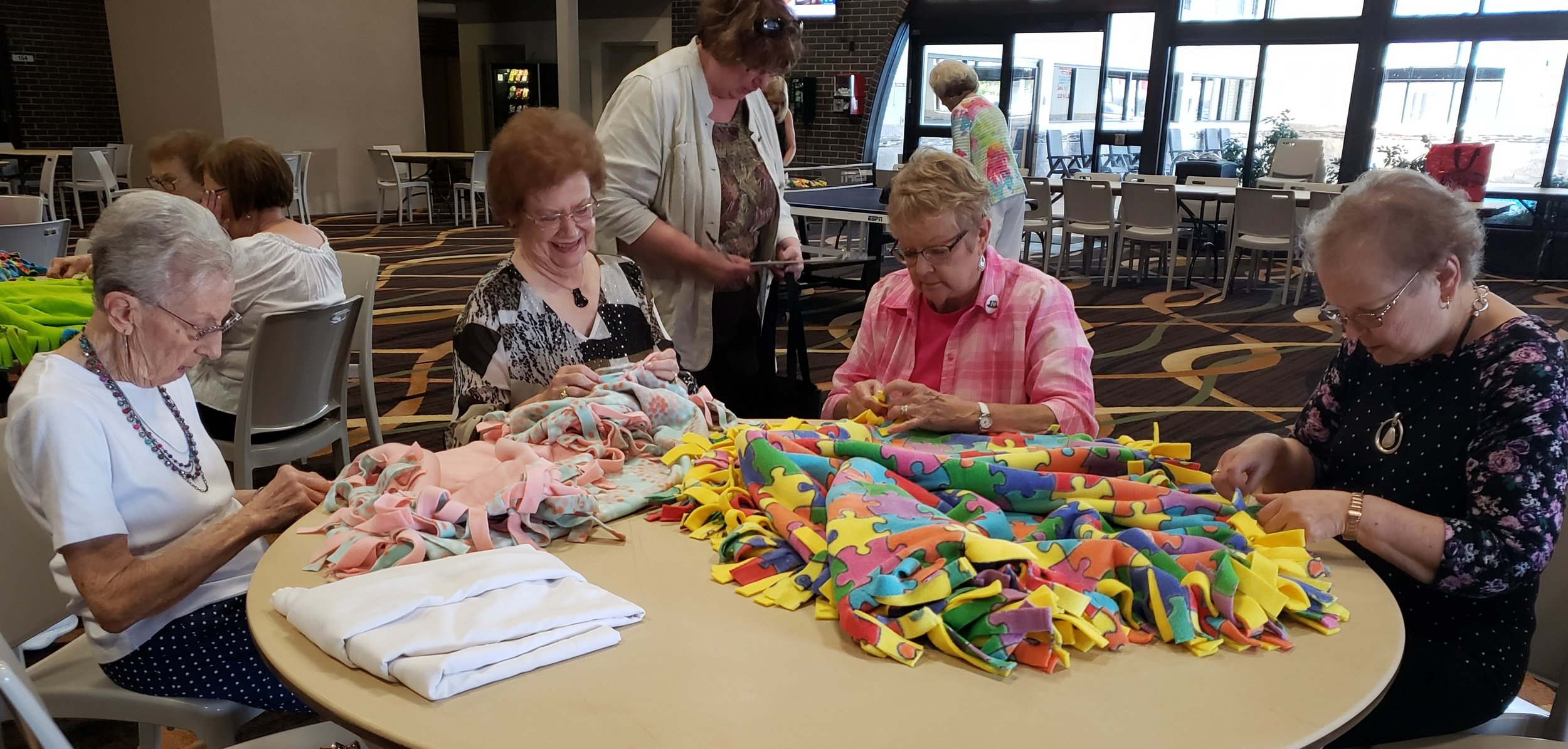 "Lois Brichacek, Marilyn Kopke, Judy Fox and Joyce Beadles-Fry work on fleece blankets for project ""Warm Embrace"" for the children in the foster care system. Pilot Club has been making quilts and tied blanket for the past 10 years.  Over 360 quilts and tied blankets have been donated to the ""Warm Embrace Prooject."""