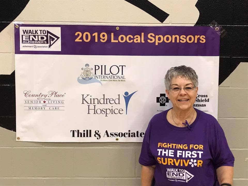 Co-captain of Pilot Club of Great Bend team, Betty Schneider, stands in front of the banner with the names of the donors for the Alzheimer's Walk. She is wearing this year's shirt for the fight against Alzheimer's. The Pilot team surpassed their goal of raising $1,000 for Alzheimer's. Great Bend Pilot Club is a major sponsor of the Walk to End Alzheimer's for the past 5 years.