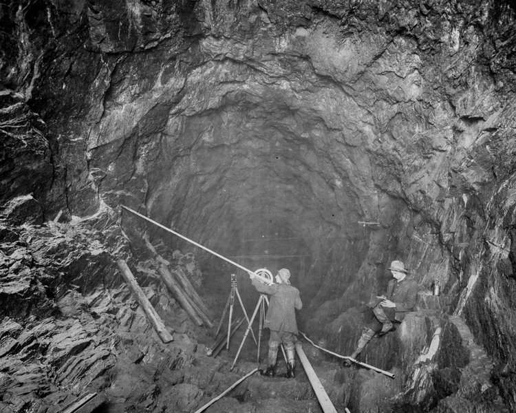 A surveyor takes cross-section measurements with a sunflower instrument in the City tunnel south of Shaft 16, New York, 1913.