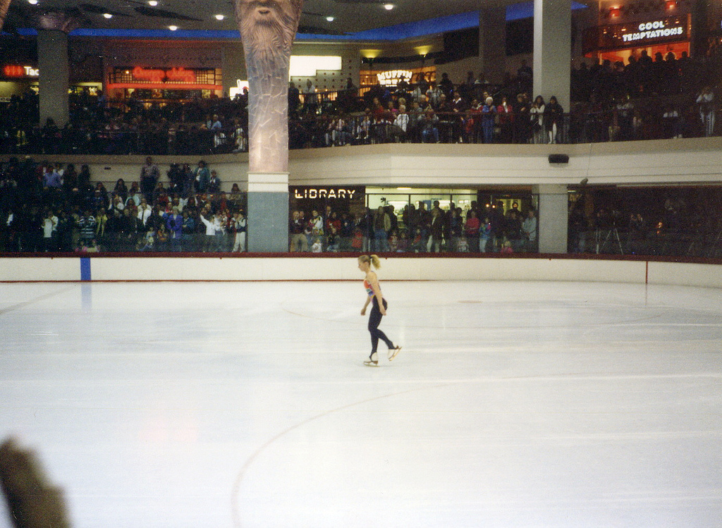 Tonya Harding skating in the Clackamas Town Center Hall in her home town. [The Library is in lights in the background, centre left