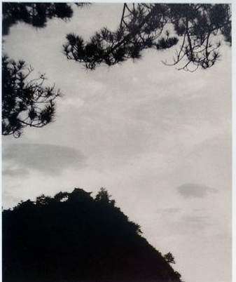 """Old postcard showing a black and white photo by Jiang Qing (Mao's wife) of the Fairy Cave in Lushan Mountain, followed by Mao Zedong's poem  The Fairy Cave :  """"Amid the growing shades of dusk stand sturdy pines,  Riotous cloud sweep past, swift and tranquil.  Nature has excelled herself in the Fairy Cave,  On perilous peaks dwells beauty in her infinite variety"""""""