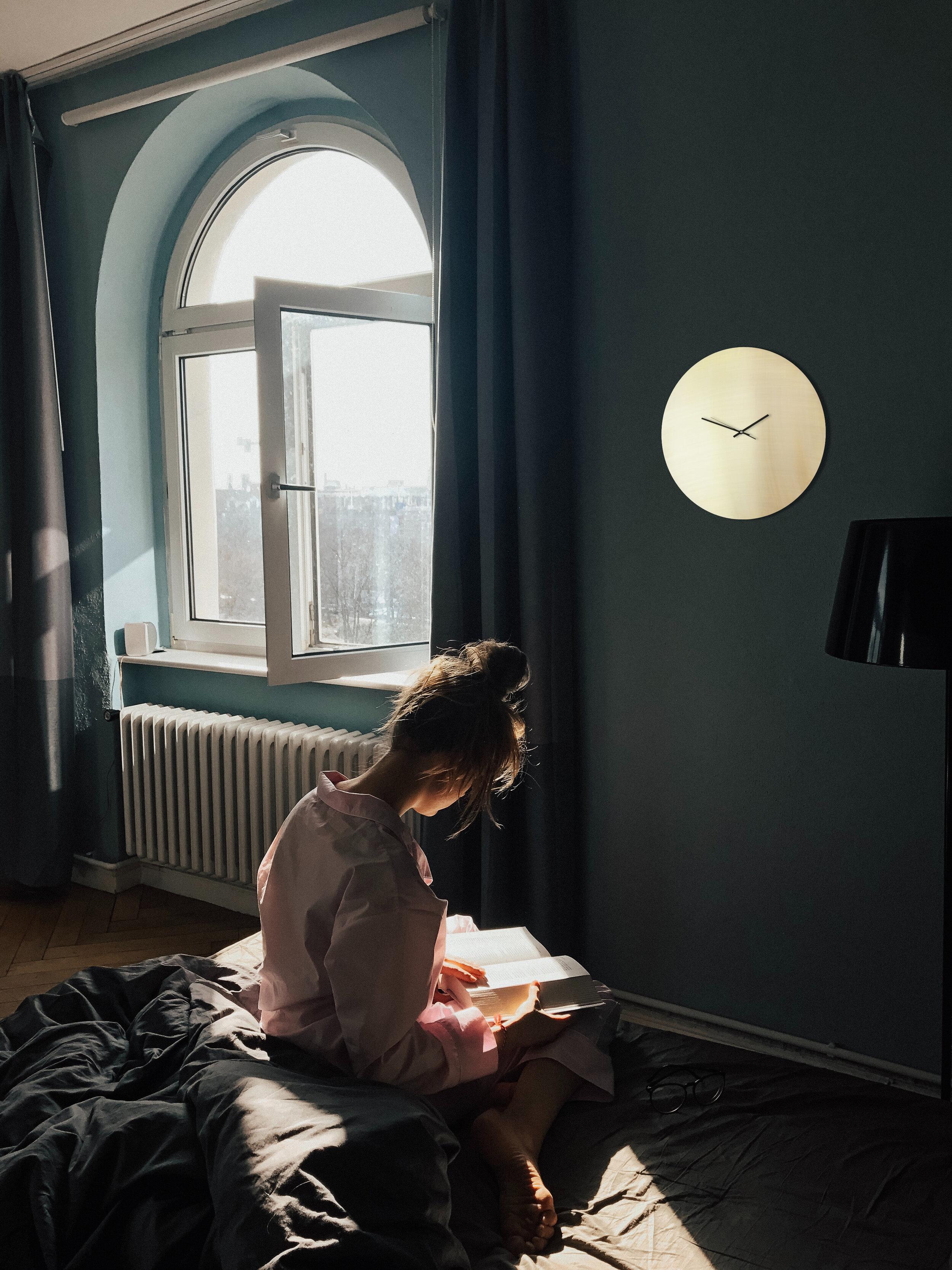 Messing Uhr Frau lesend offenes Fenster.jpg