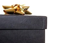 A black gift box with a gold bow