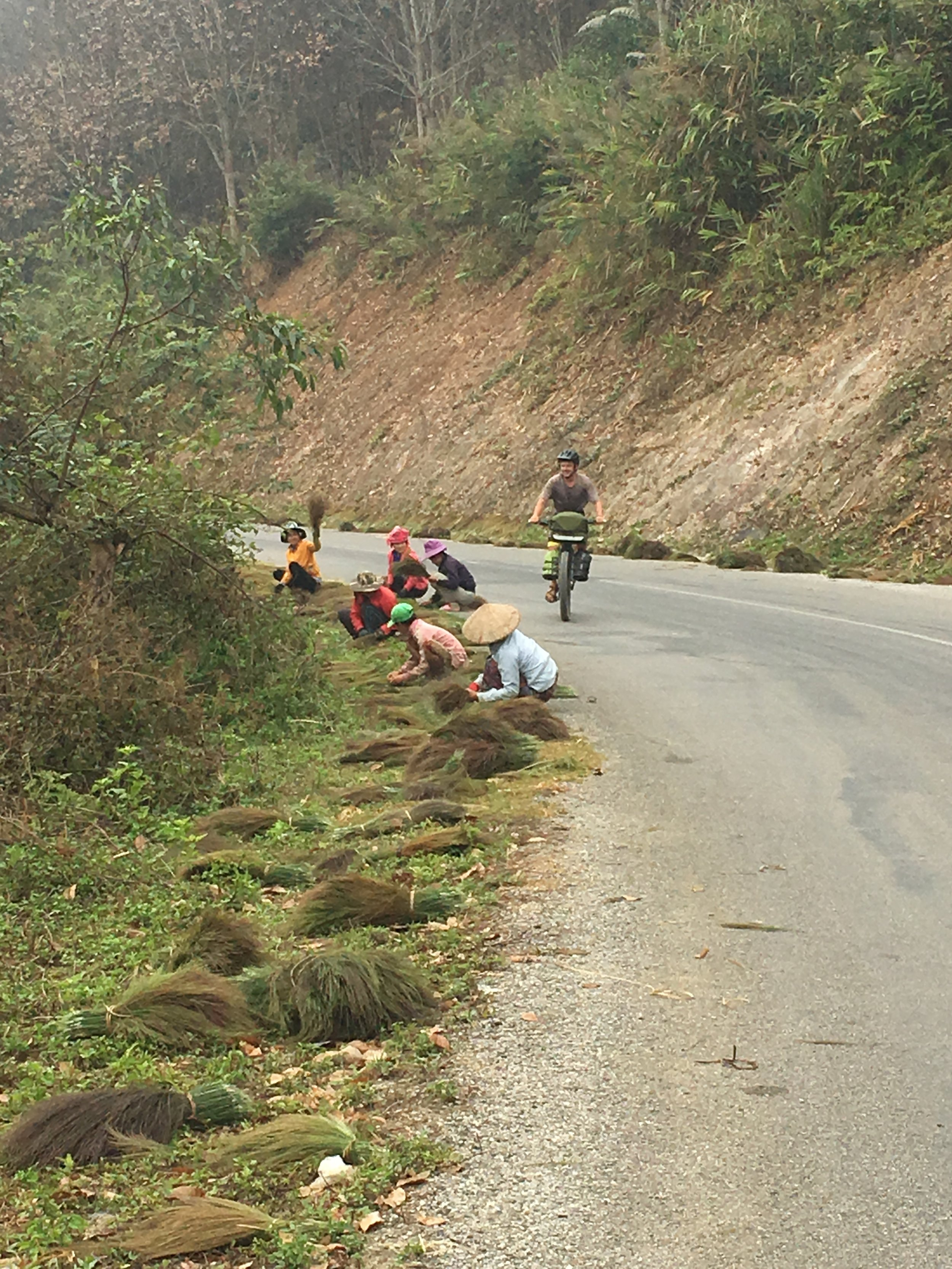Christian cycling passed the local Laos women working on the side of the road. The woman at the back had the biggest smile on her face as we rode passed