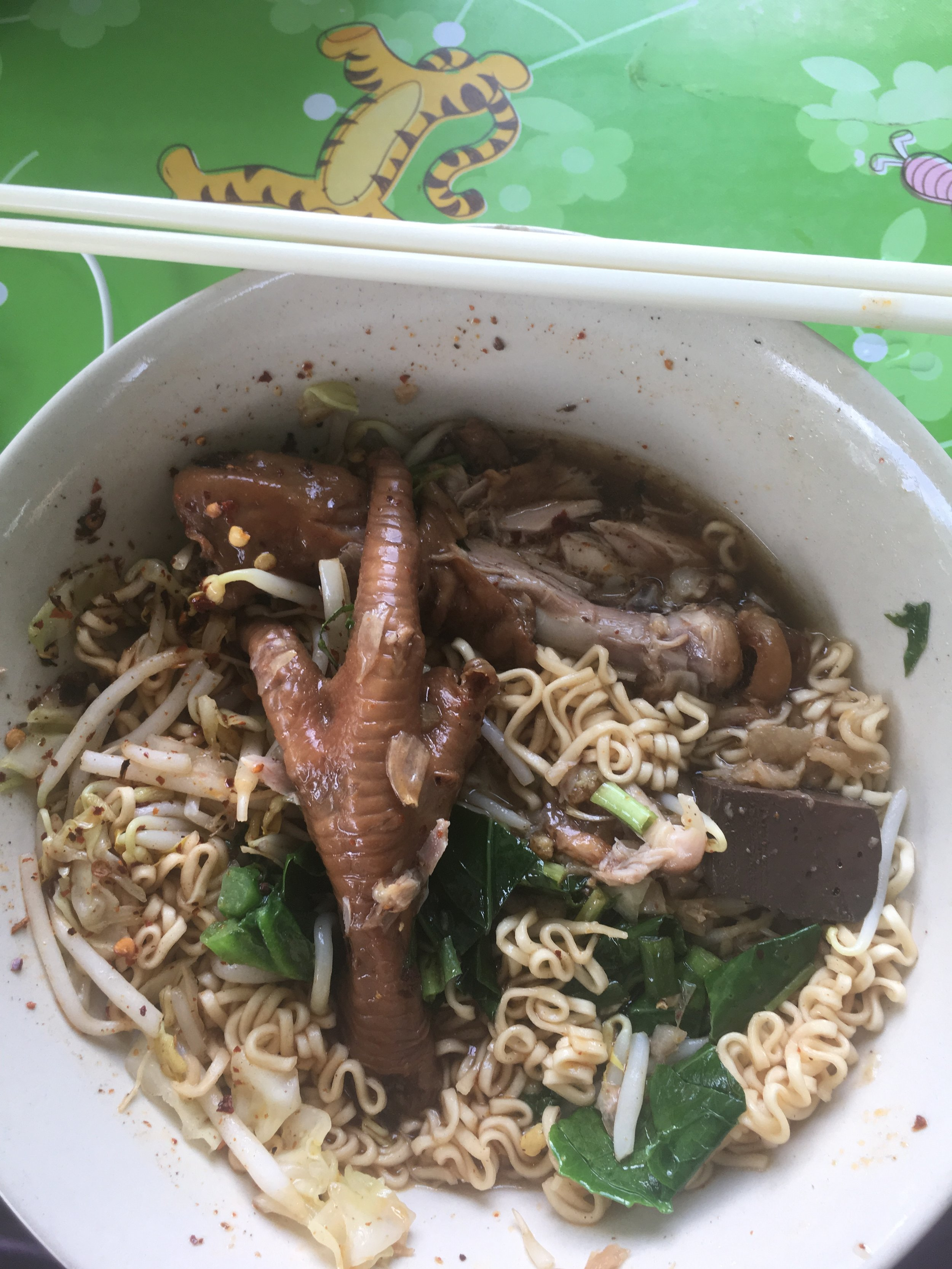 Instant noodle, cow blood, cow blood jelly and chicken feet soup. Instant noodles, when used in the right way can create a great meal. Notice the Winnie the Pooh table mat. This restaurant was on the side of a fairly quiet road.