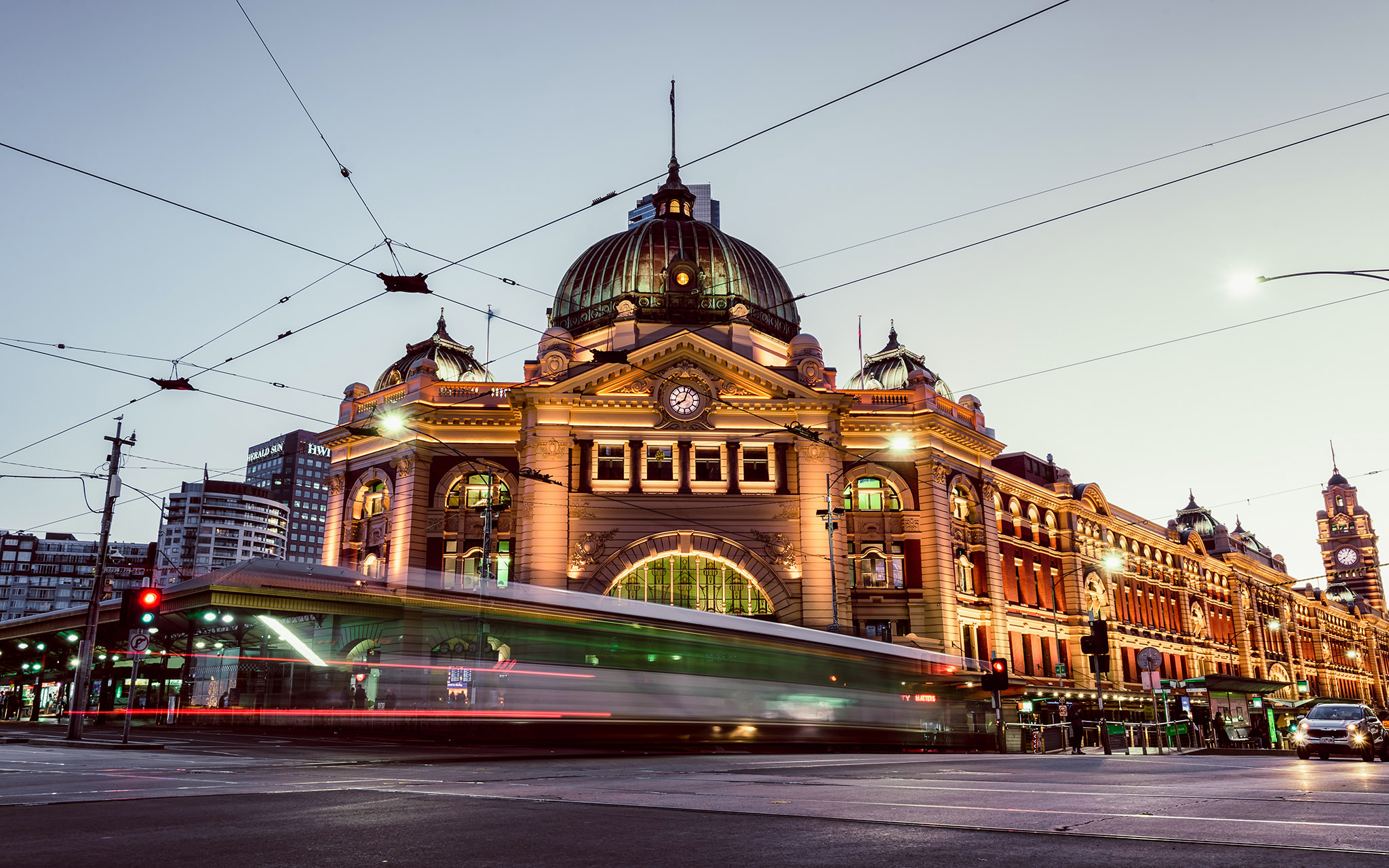 The sun sets behind Flinders Street Station in Melbourne as a tram zooms by - Photo by Paul Tadday