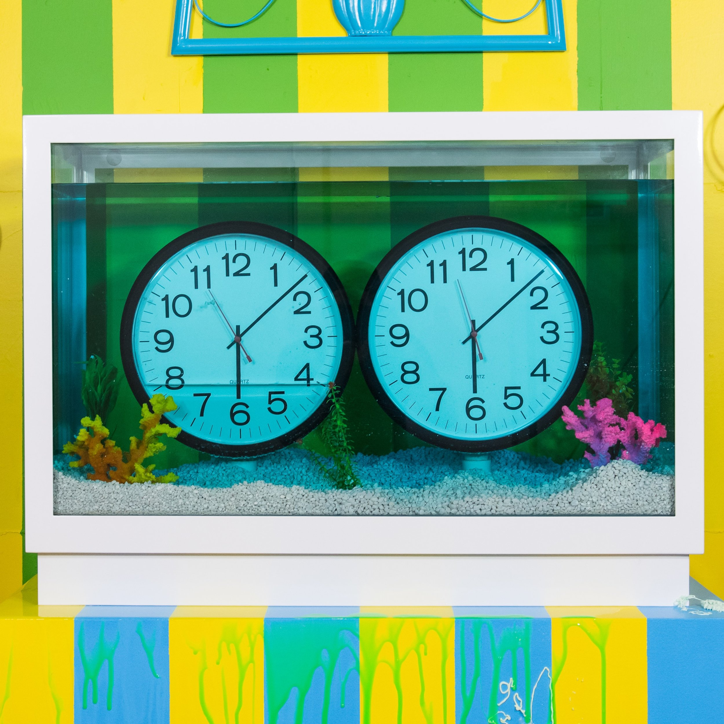 "I die for all mysterious things. (after Félix González-Torres and Damien Hirst)   2018  clocks, glass tank, powder coated steel frame, pipes, spray paint, wiring, batteries, switch, water, food coloring, aquarium gravel, fake plants and coral  28"" x 40"" x 13"""