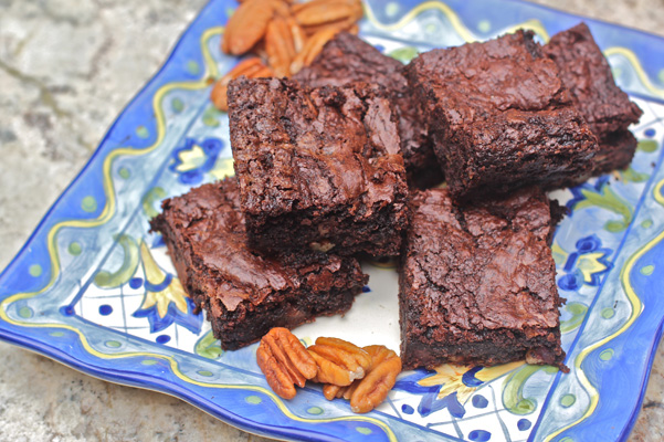 Triple Chocolate Brownies with Pecan Flour      Author: Dédé Wilson      Makes: Makes 32 brownies        Ingredients      ½ cup all-purpose flour      ¼ cup Oliver Farm pecan flour      1½ teaspoons baking powder      ½ teaspoon salt      1 cup (6 ounces) semisweet chocolate morsels/chips      1 cup toasted pecan halves, finely chopped      8 ounces semisweet chocolate, finely chopped, such as Callebaut or Ghirardelli      1 cup (2 sticks) unsalted butter, at room temperature, cut into pieces      3 ounces unsweetened chocolate, finely chopped      1 cup plus 2 tablespoons sugar      4 large eggs, at room temperature      1 tablespoon vanilla extract      Instructions      Position rack in center of oven. Preheat oven to 350°F. Coat a 9 x 13-inch baking pan with nonstick spray; set aside.      Whisk flour, pecan flour, baking powder and salt together in a large bowl. Stir in chocolate chips and all of the pecans to coat; set aside.      Melt 8 ounces of chopped chocolate, butter and unsweetened chocolate in a medium bowl over simmering water or in a microwaveable bowl. Cool to lukewarm.      In a large bowl, gently whisk together the sugar, eggs, and vanilla. Stir in the lukewarm chocolate mixture into the egg mixture and allow to cool to room temperature. Fold then stir in the dry mixture just until combined. Pour into prepared pan.      Bake for 30 to 35 minutes, rotating pan front to back once during baking, until a toothpick inserted in the middle comes out with moist crumbs clinging. Do not over bake. Cool on rack. Cut into squares; best eaten within 3 days. Store in airtight container at room temperature in single layers separated by parchment paper or foil. May be frozen up to 1 month, double wrapped in plastic and then foil.      Bakepedia Tips      I cannot stress enough how tender and delicate these can be. Take care when cutting and transferring to plates or storage containers to minimize crumbling or breaking.      Photo: Dede WIlson