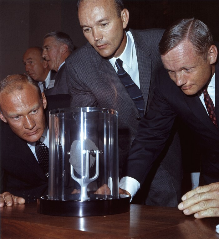 trio examines moon object (with suits on).jpg