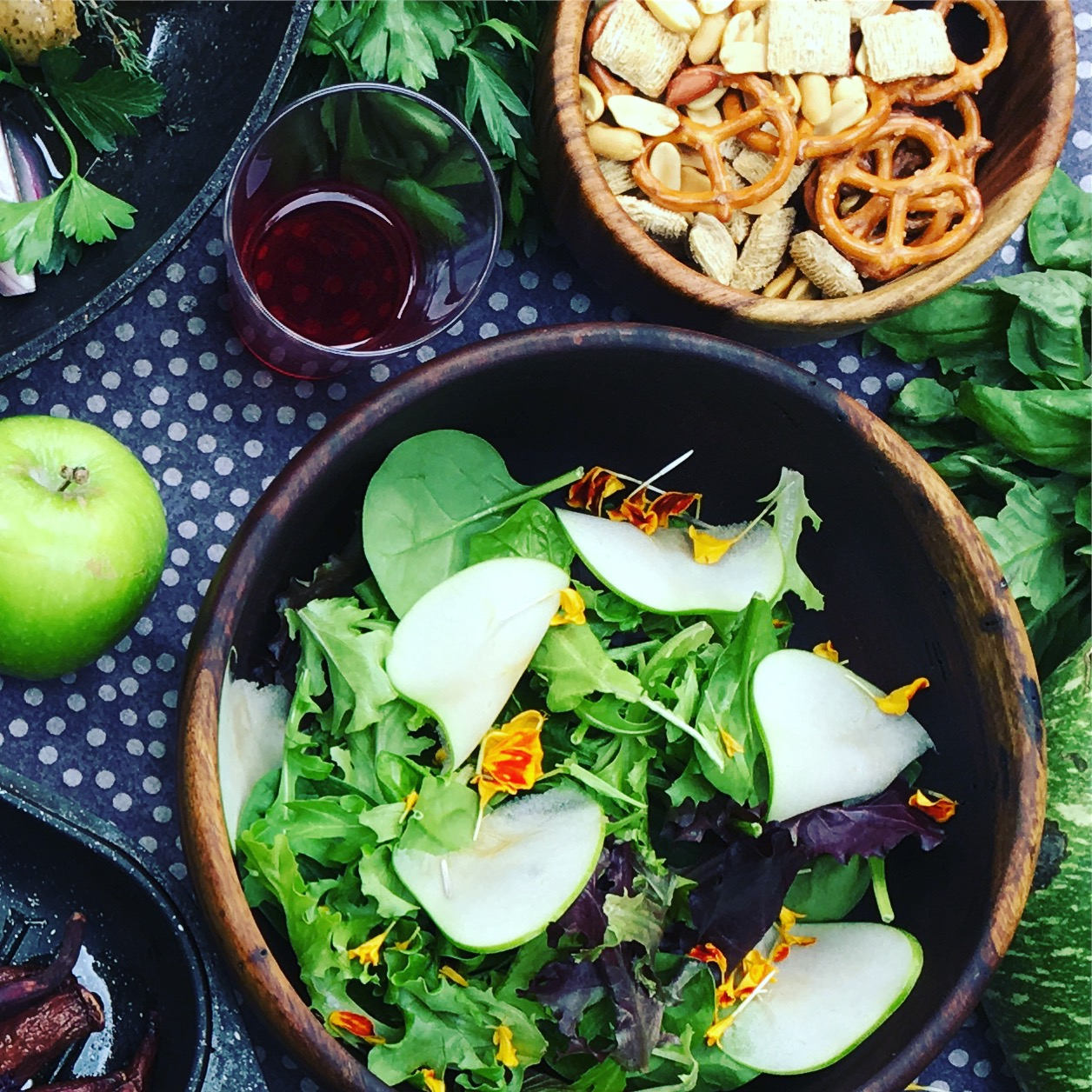 Think about contrast in texture, color, and ingredients. This salad has finely-sliced, ripe apples, mixed greens for color and texture variation, edible flowers. By itself, all this tastes delicious and fresh. But it also contrasts the sausages ...