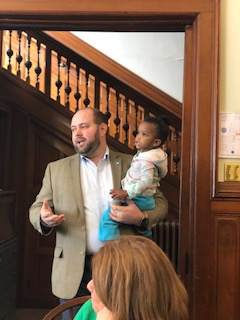 Executive Director Bronson Kopp speaks at our 4th Anniversary luncheon holding Kimmy, one of our residents.jpg