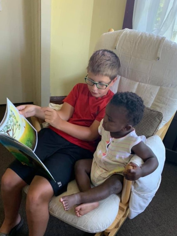 A young Joseph's House volunteer reading to one of our younger Joseph's House gifts of life.
