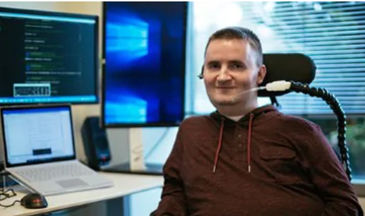 Smiling man using a respiration/tracheal tube for assisted ventilation in a wheelchair while using Microsoft technology and programming software displayed on multiple monitors  Microsoft Accessibility (2018). Retrieved from  https://www.microsoft.com/en-us/accessibility