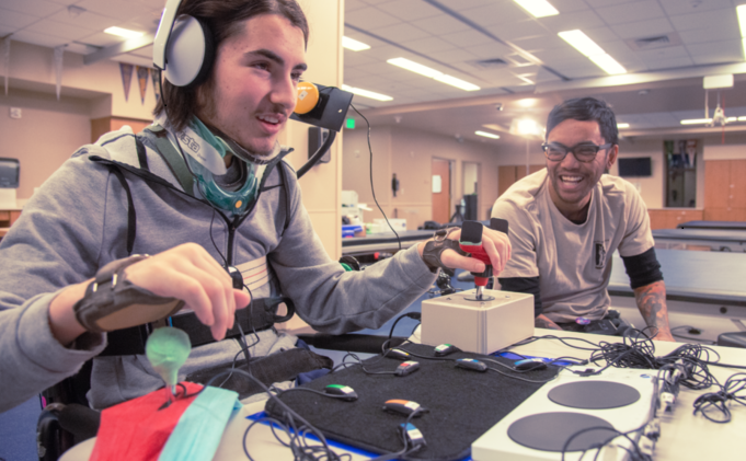 Smiling adolescent boy in a wheelchair and neck brace wearing Microsoft headphones and using the Xbox Adaptive Controller to play video games with a friend.