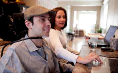 Smiling man using an adaptive mouth device connected to his wheelchair while working on his laptop with another woman who is also smiling and working on her laptop next to him