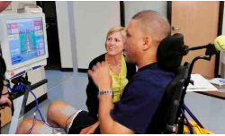 Young man in a wheelchair playing a physically interactive video game at Shepherd Center while a research PI & physical therapist observes and moderates his activity.