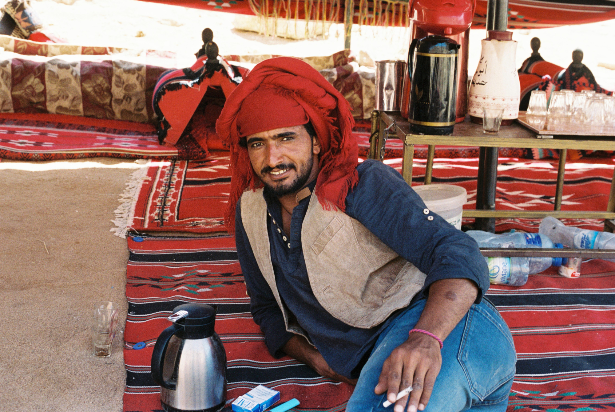 A Bedouin guide inside the ancient city of Petra relaxes with tea and a cigarette under the hot afternoon sun.