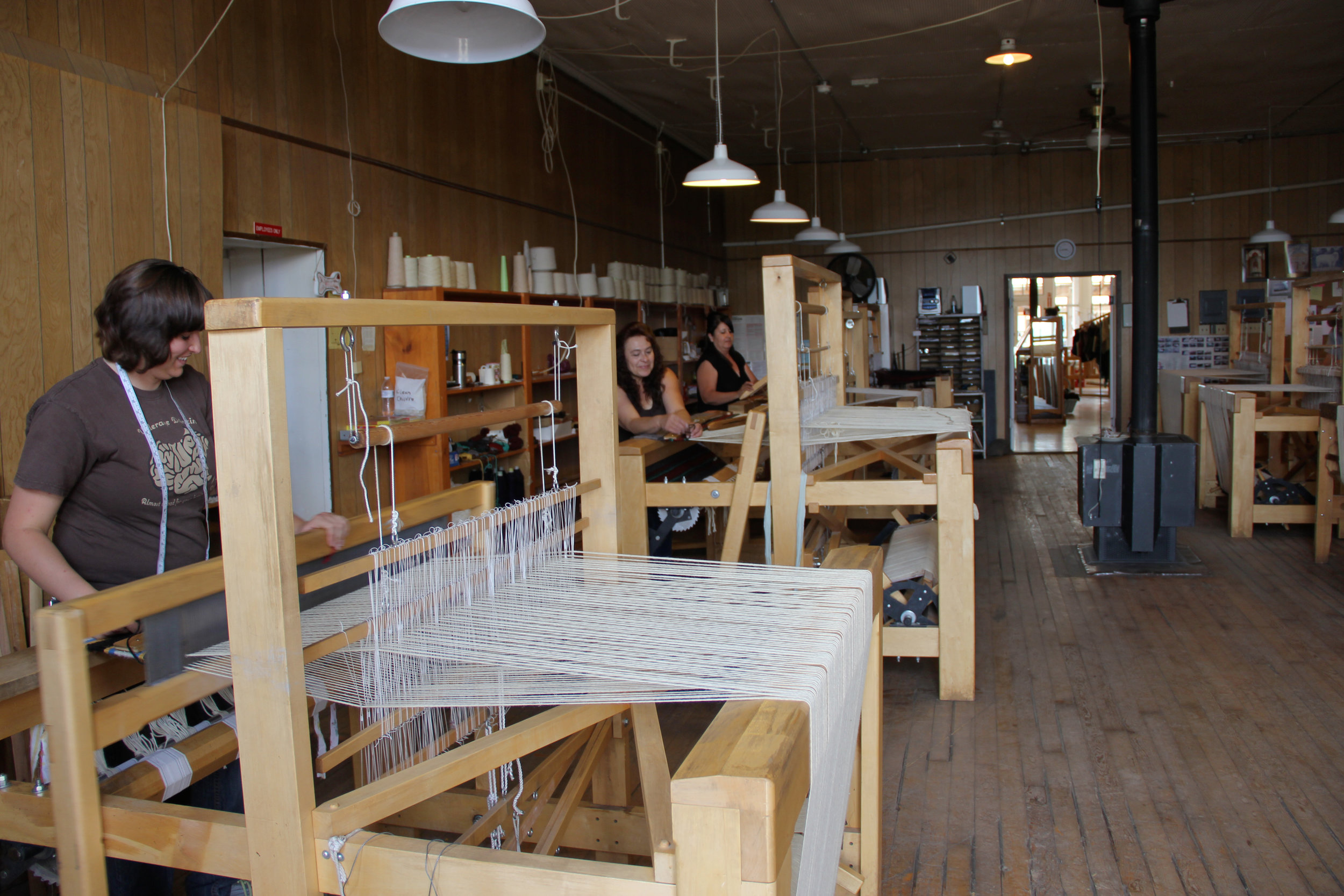 L-R: Aubrey, Sophia and Mary weave on the Tierra Wools looms