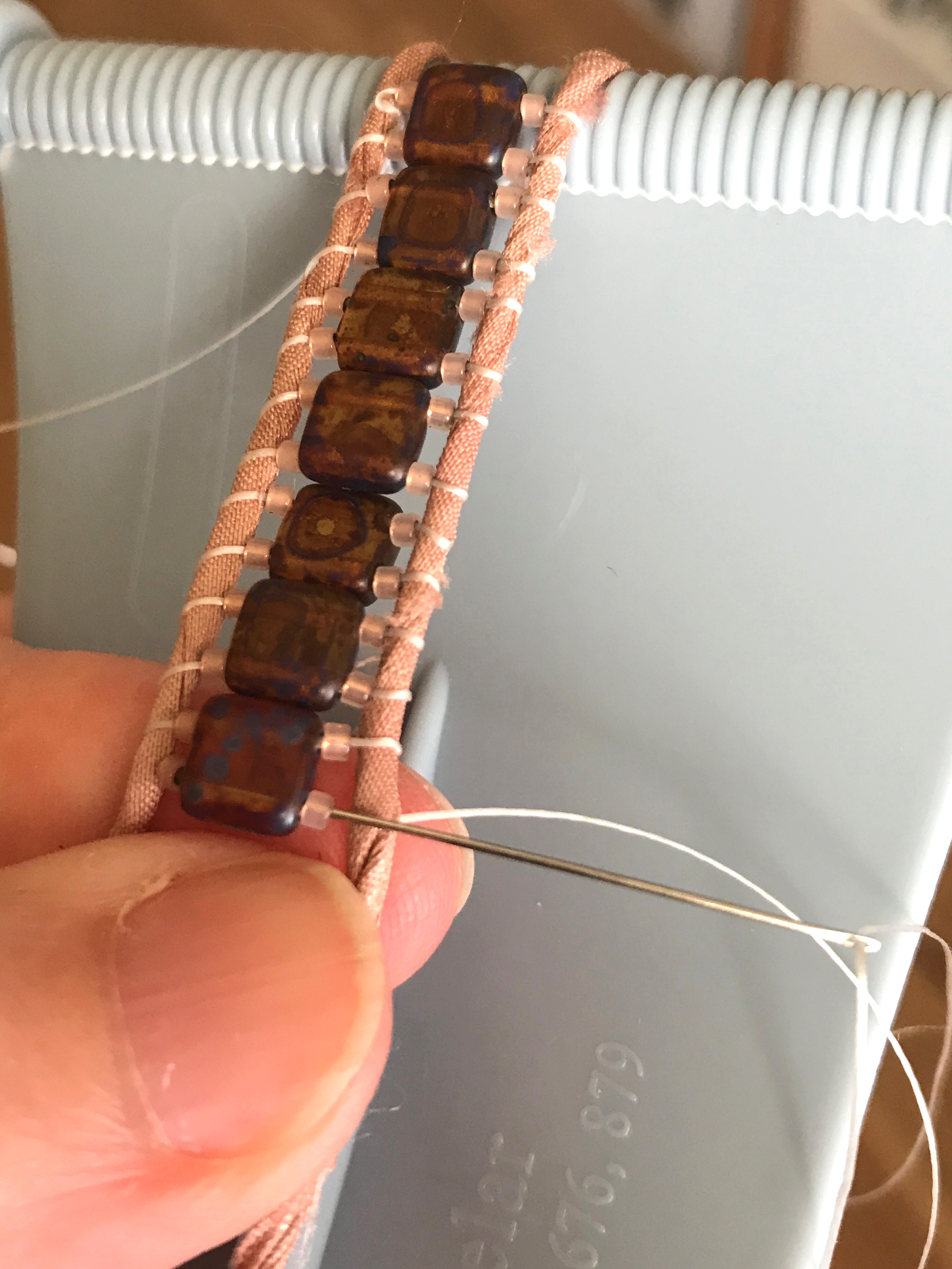 10. Use your finger again to nestle everything nicely between the ribbon strands. Bring your needle up and to the top of the work and thread it back—right to left—through all three beads with the needle remaining on top of the left strand.