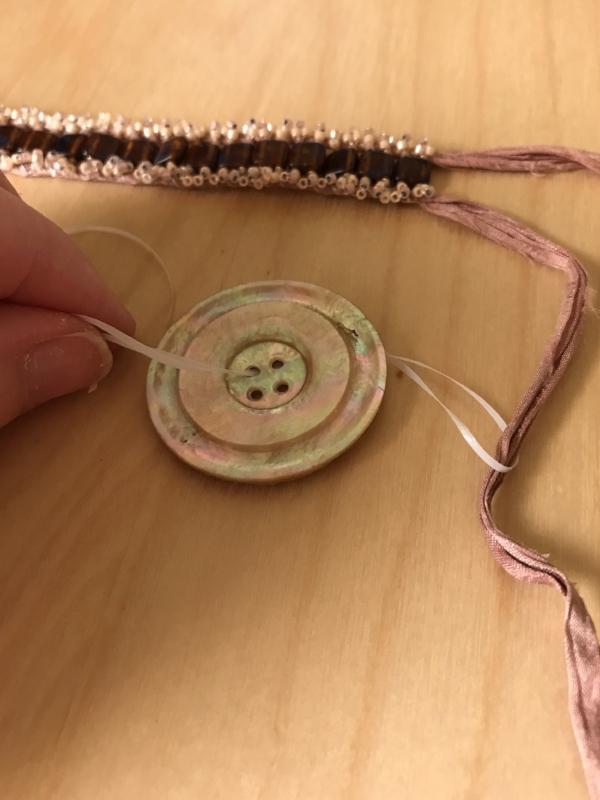20. Thread one ribbon strand through the floss loop.