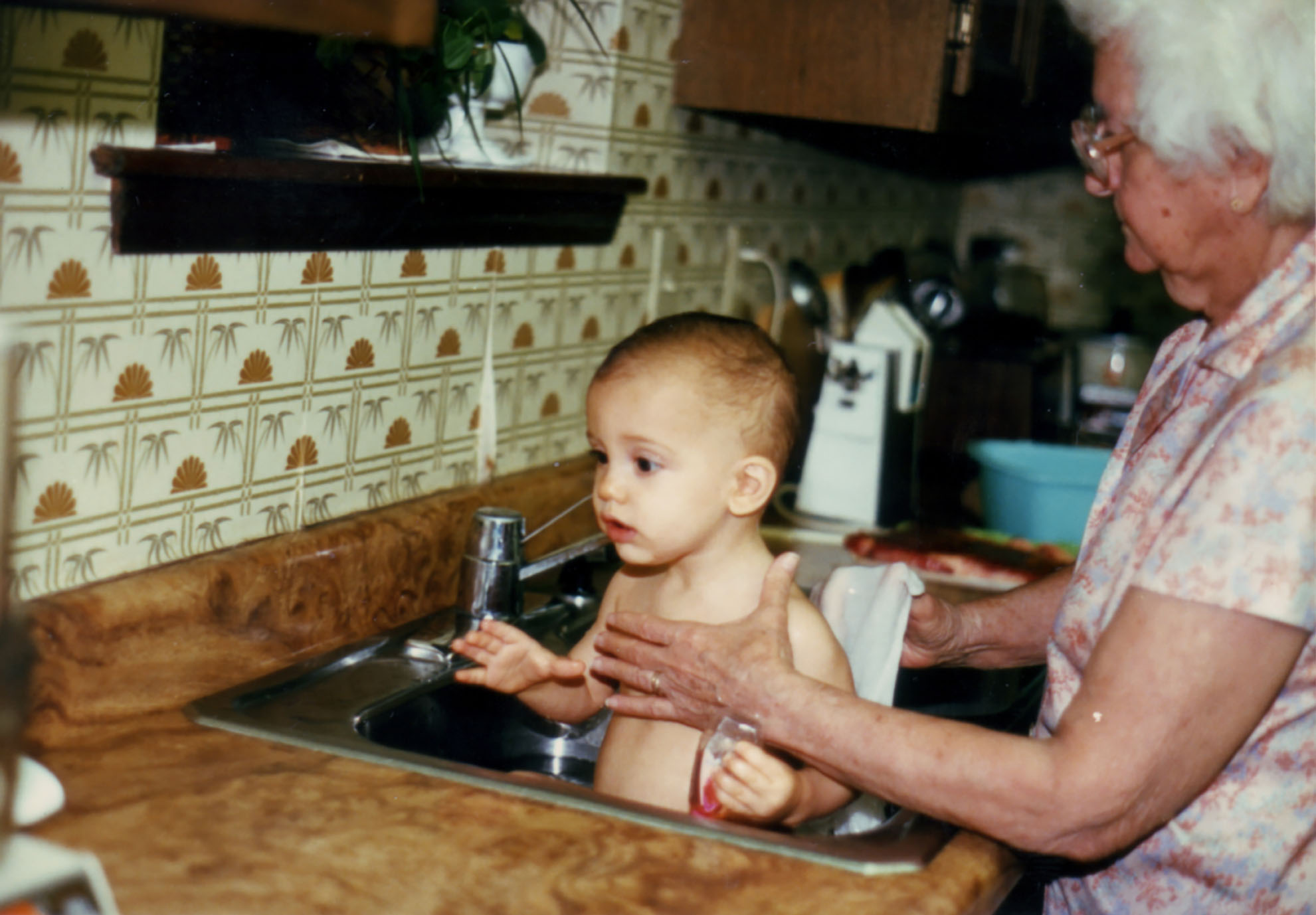 a photo of my older brother eric getting a sink bath from our great grandmother, circa 1986-ish