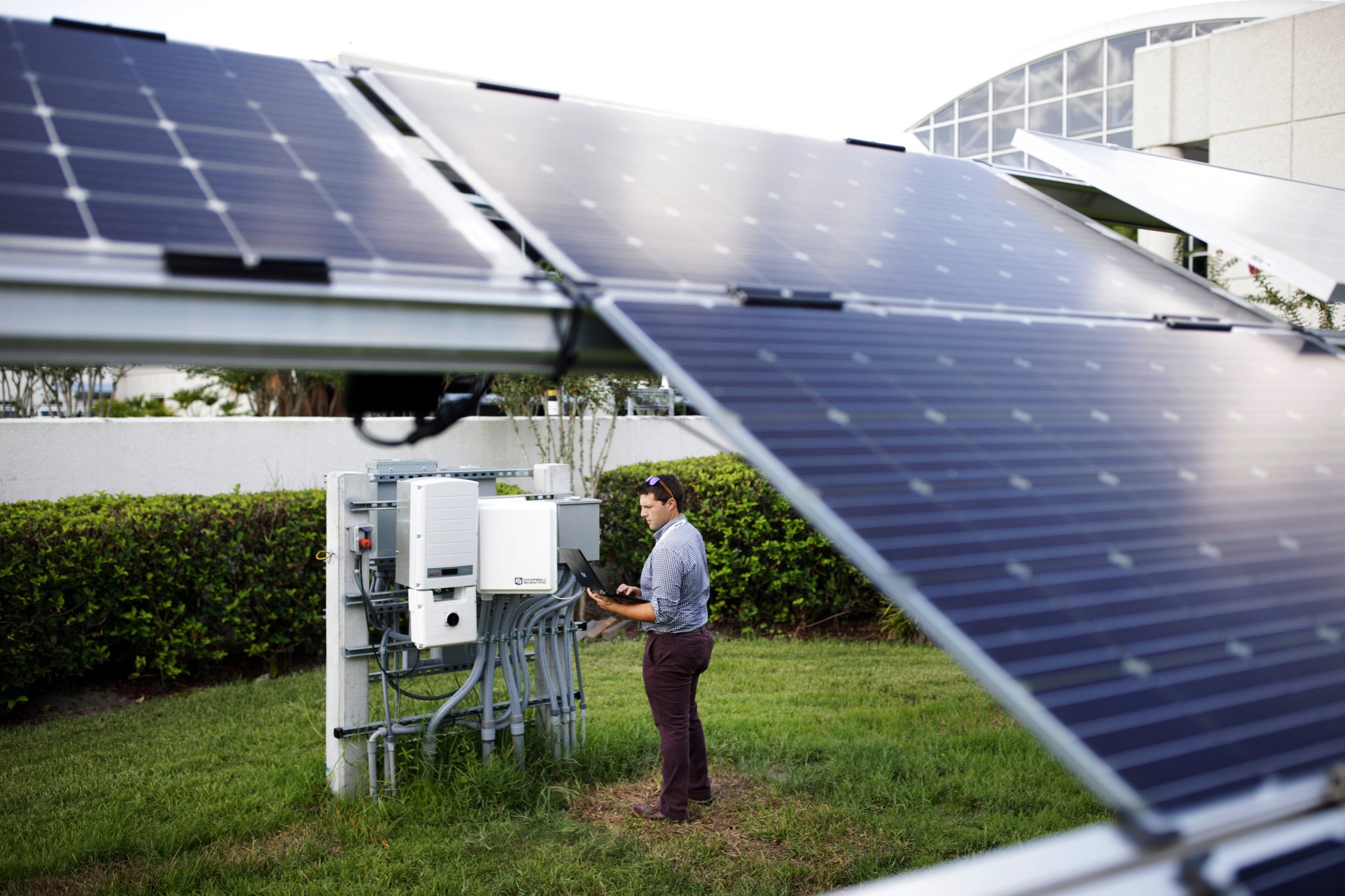 Engineer with the Orlando Utilities Commission, examining data at a solar test site installed by Power Production Management. Photo taken by New York Times, and full article can be found here:  https://www.nytimes.com/2018/08/30/business/energy-environment/orlando-carbon-climate.html