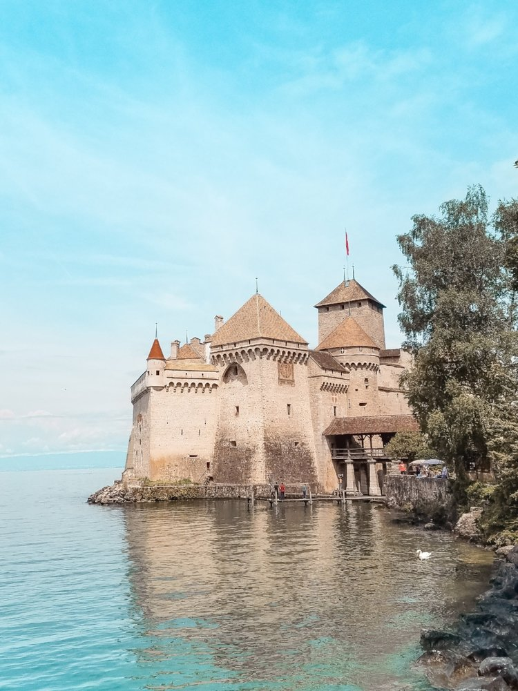The Chillon Castle in Montreux, Switzerland, sits on a turquoise lake with a mountainous background and swans floating by.