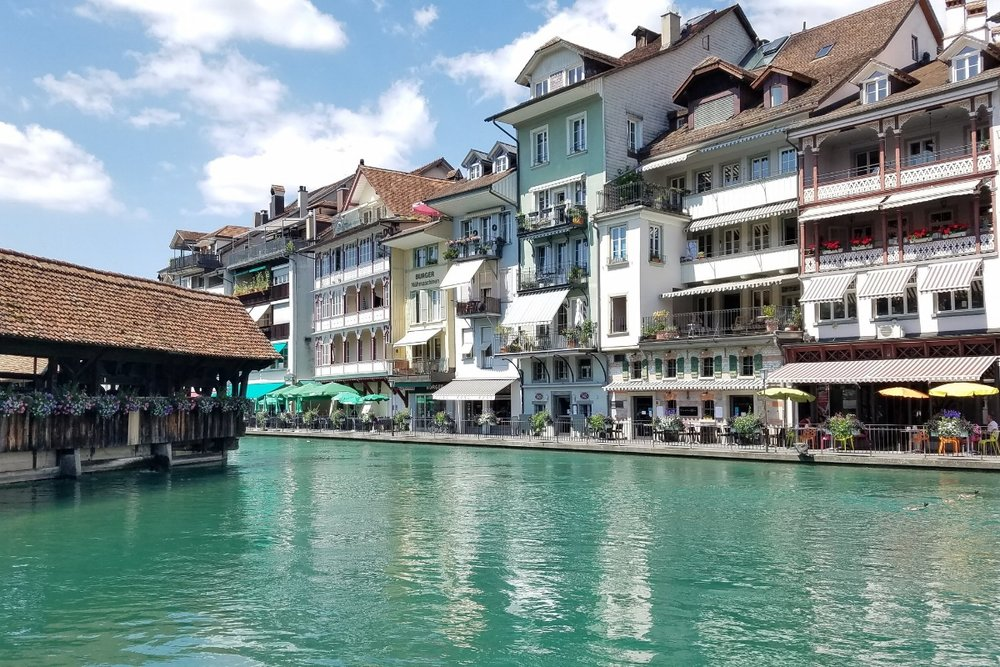 Emerald waters flow alongside colorful buildings in lakeside Thun, where you'll find tons of shopping and a pretty, white castle. This Switzerland road trip itinerary will help you plan your vacation to see Thun and other picturesque villages, castl…