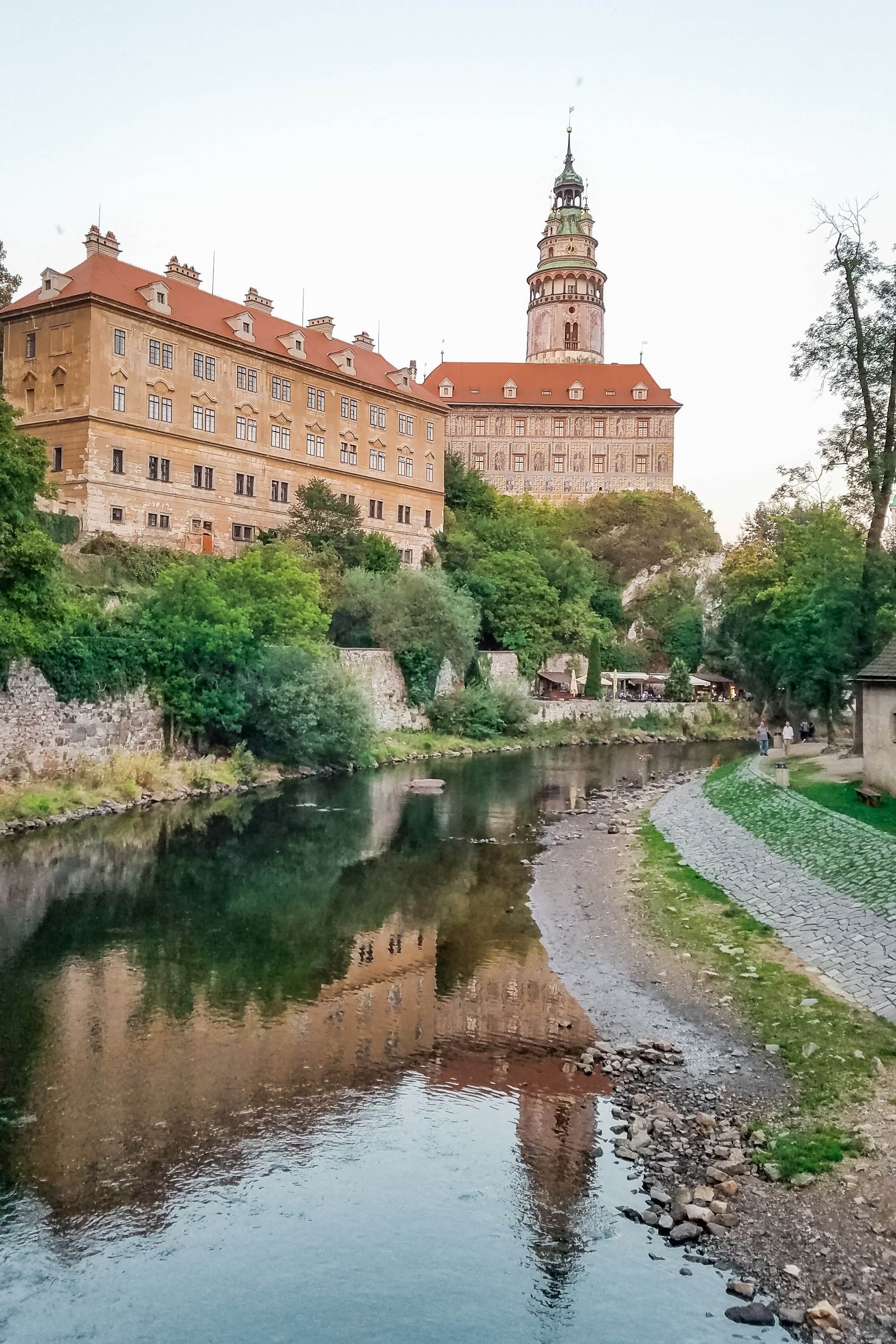 The Cesky Krumlov Castle and tower reflects on the surface of the Vltava River near downtown Cesky Krumlov. You can stroll and dine along the riverbank or rent rafts for a thrilling excursion on the water.