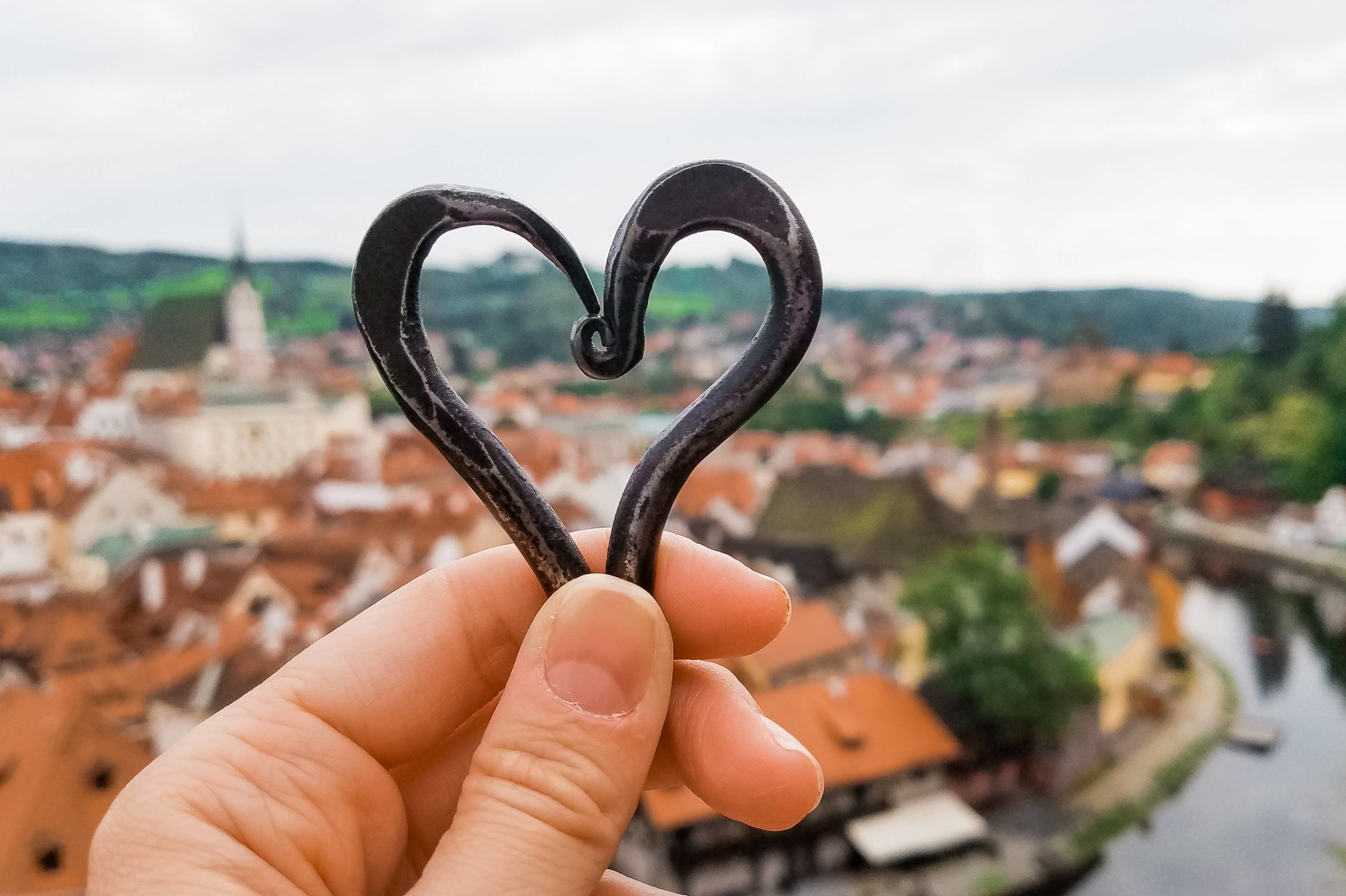 The view from the Cesky Krumlov tower looking over downtown and St. Vitus Church framed by an iron heart made by the local blacksmith.
