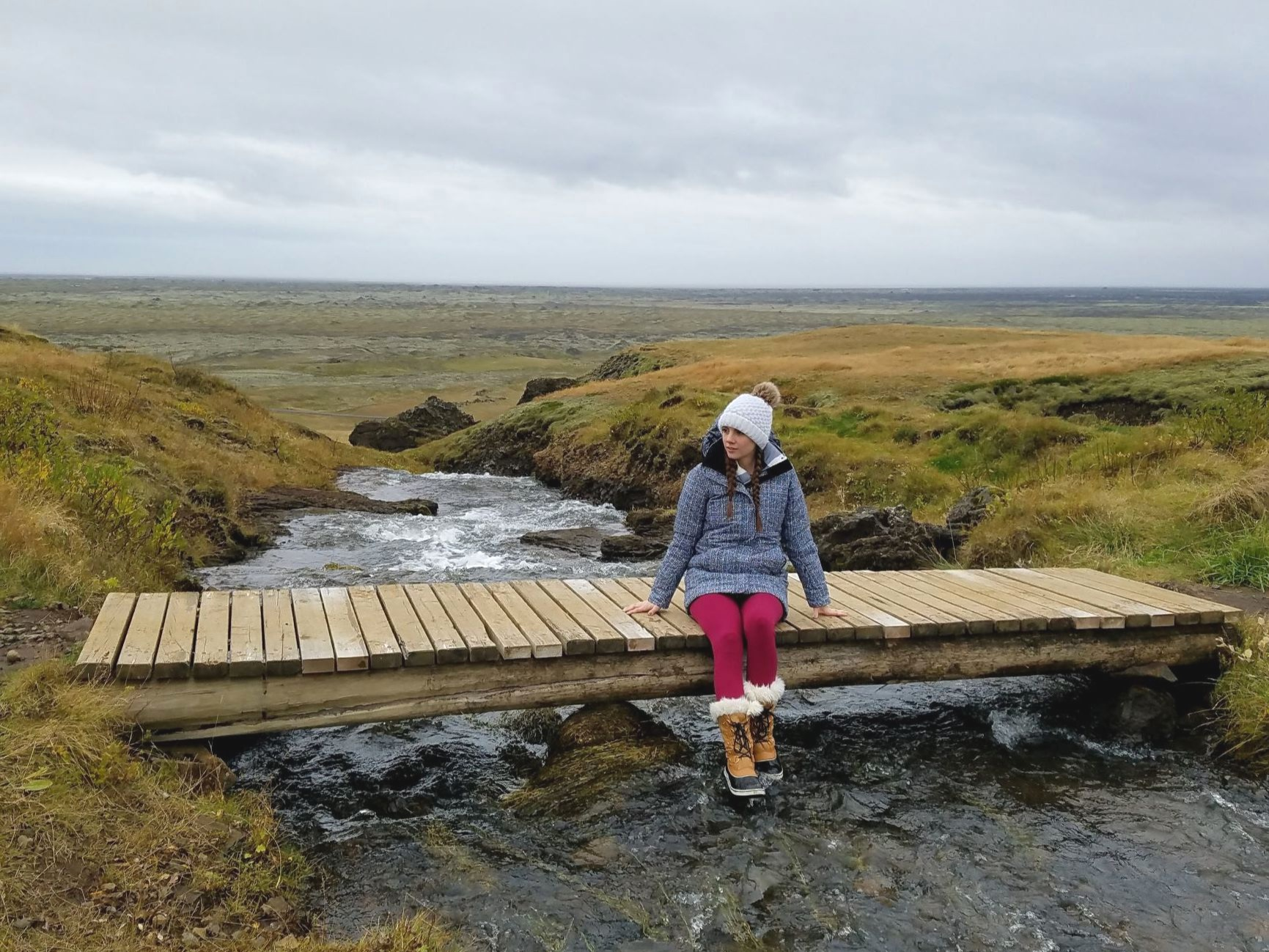 This coat and boots outfit on a stream in Iceland shows what to wear in Iceland.