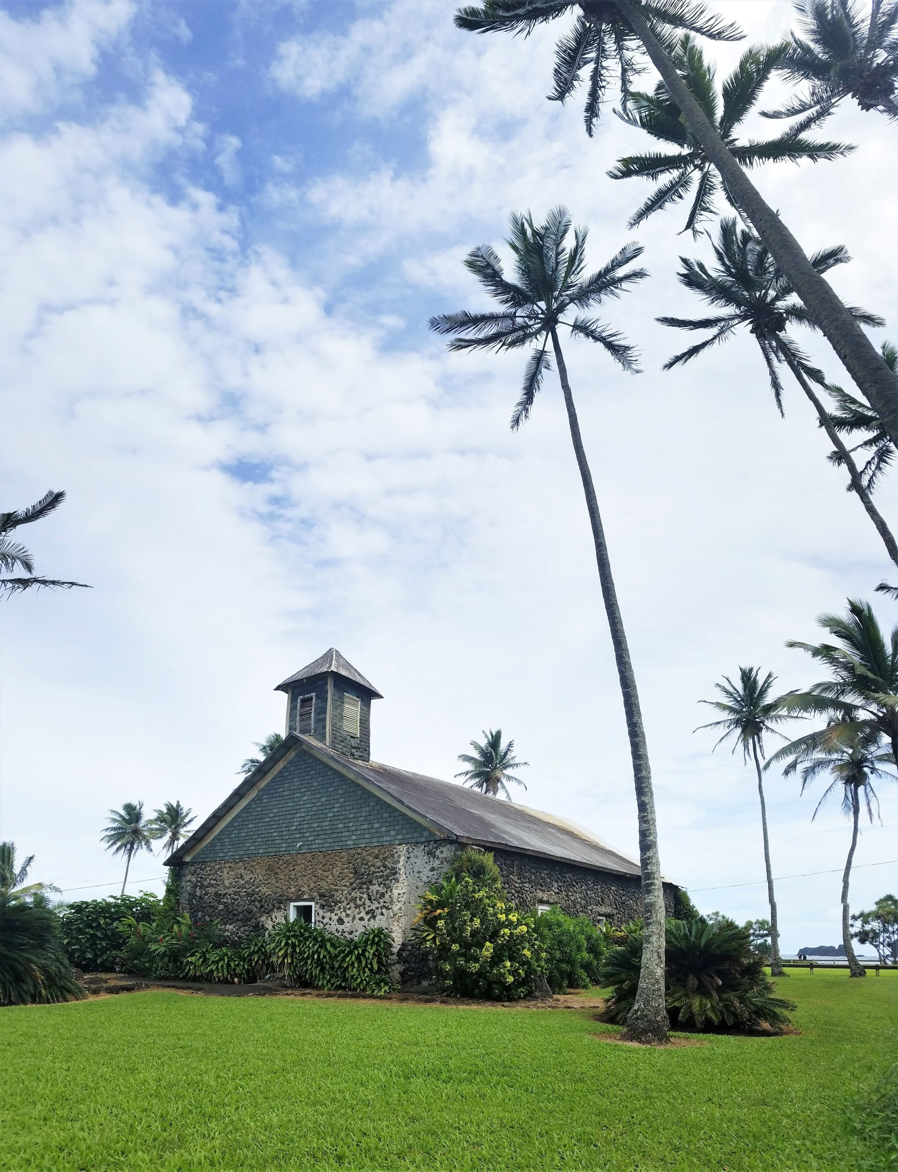 A stone church surrounded by palm trees by the ocean is a stop in this Road to Hana guide.