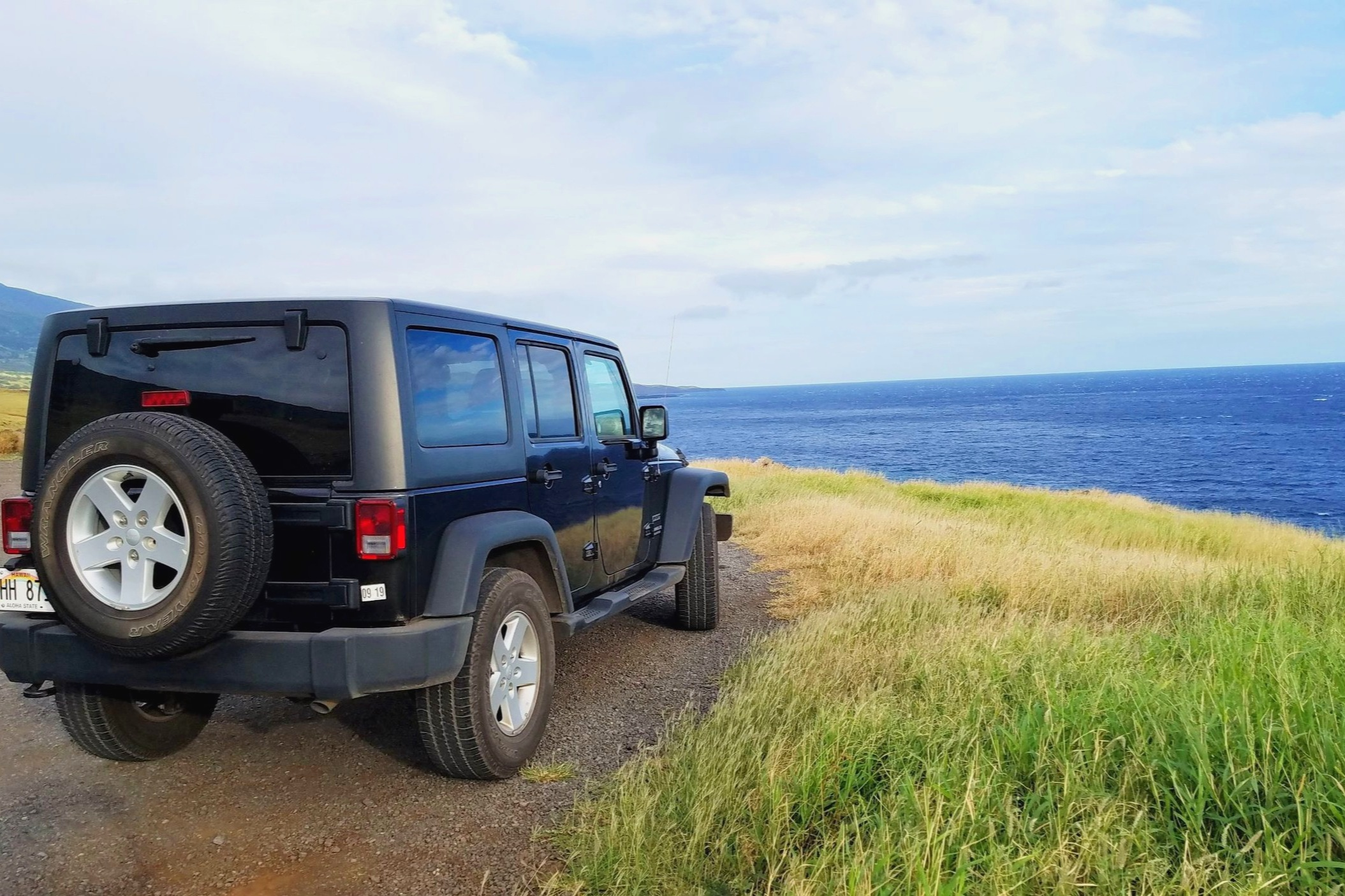 A black jeep overlooks the blue ocean on the Road to Hana.